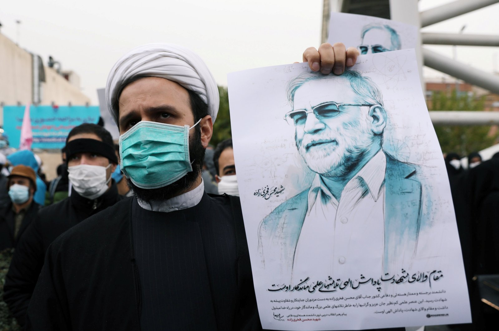 A protester holds a picture of Mohsen Fakhrizadeh, Iran's top nuclear scientist, during a demonstration against his killing in Tehran, Iran, Nov. 28, 2020. (REUTERS Photo)