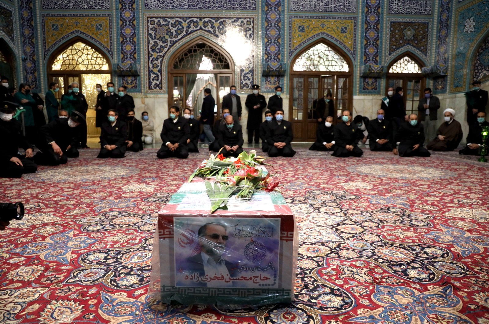 A handout picture provided by the Iranian defense ministry shows family members and officials praying over the coffin of slain Iranian nuclear scientist Mohsen Fakhrizadeh inside the Shrine of Imam Reza, during a funeral ceremony in the city of Mashhad, northeastern Iran, Nov. 29, 2020. (EPA Photo)