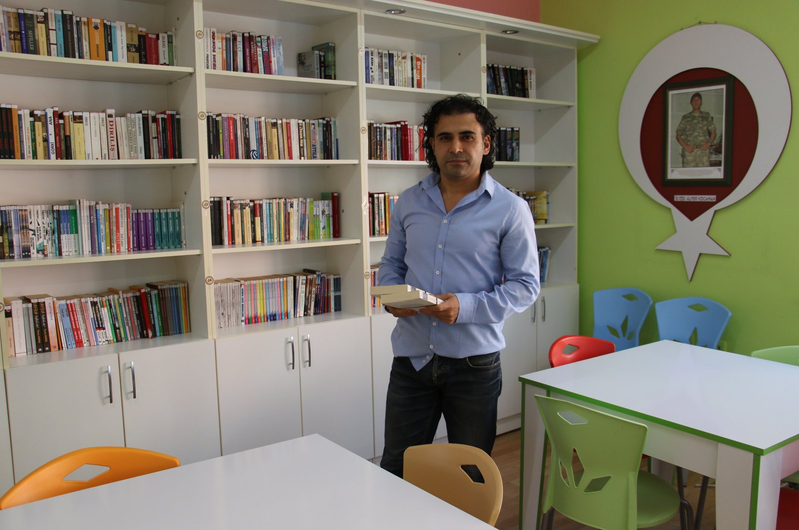 Sercan Kürklü of the Martyrs Libraries Collective poses with donated books in a library built in the memory of a martyred Turkish soldier, Ankara, Turkey, Nov. 29, 2020. (IHA Photo)
