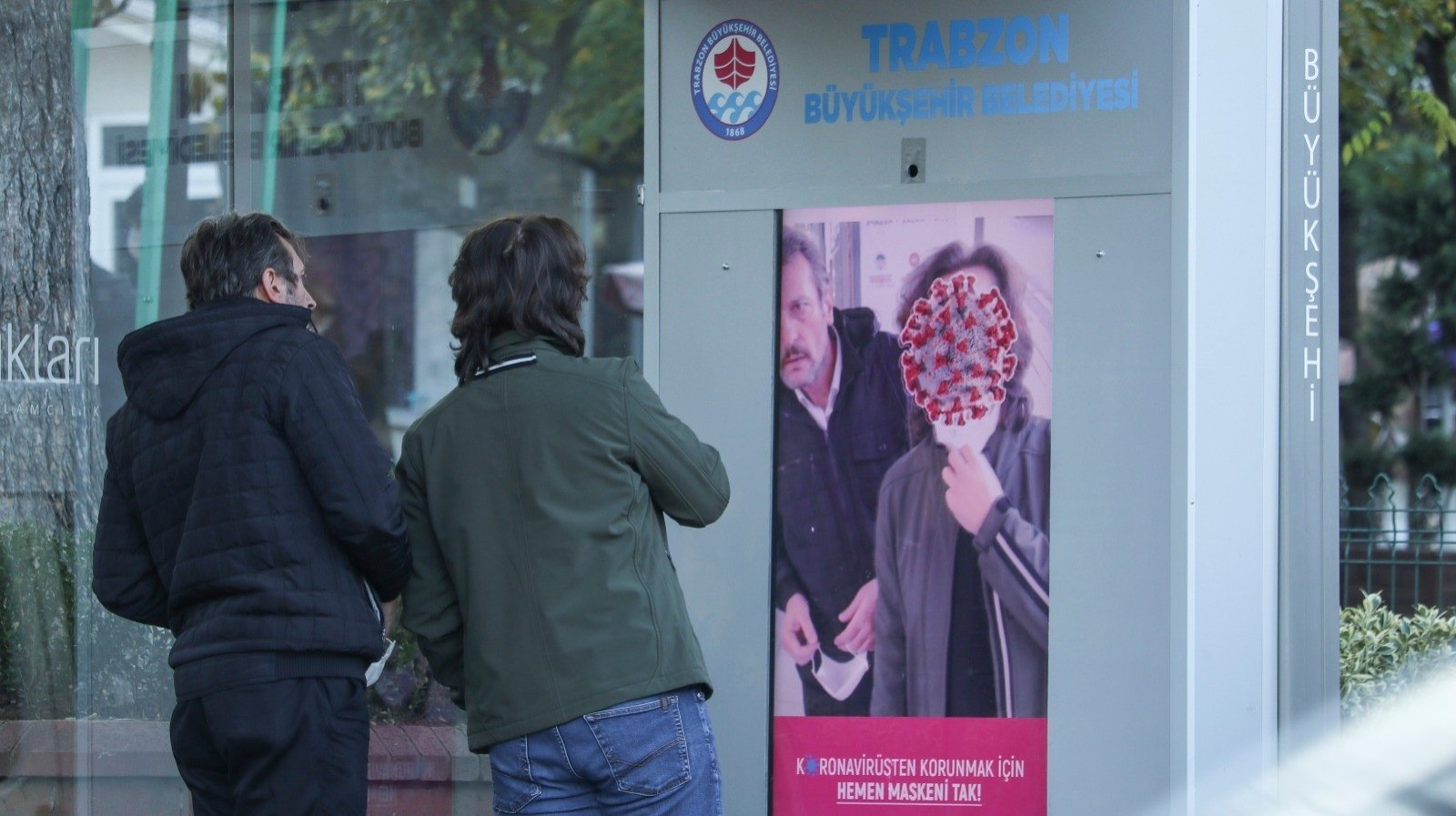 """Two men not wearing masks look at the screen which has a message reading """"Wear your mask immediately to protect yourself from the coronavirus,"""" in Trabzon, northern Turkey, Nov. 30, 2020. (IHA Photo)"""