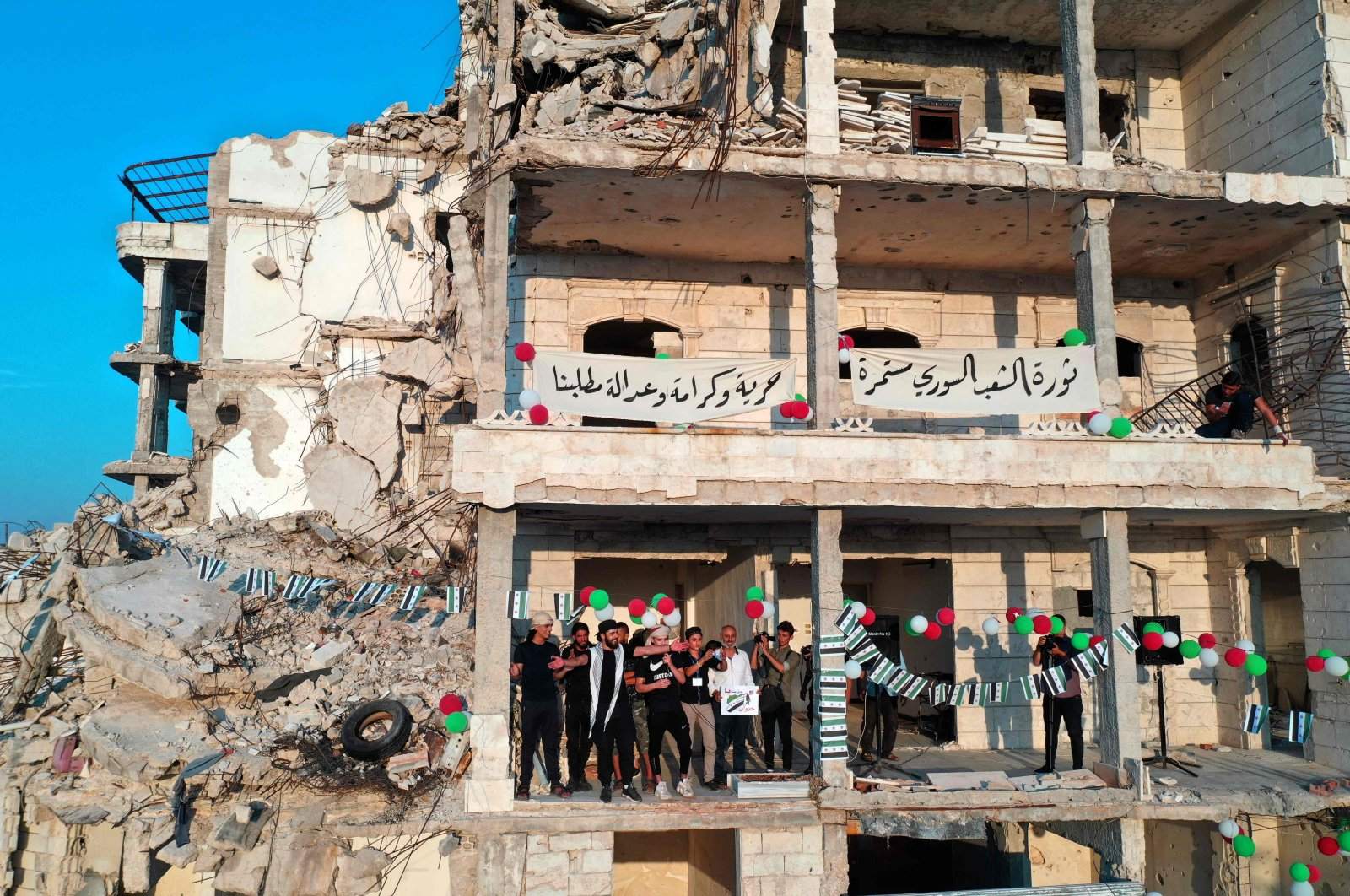 Chanters lead an anti-regime demonstration amid destroyed buildings in the town of Ariha in Syria's opposition-held northwestern Idlib province, Aug. 28, 2020. (AFP Photo)