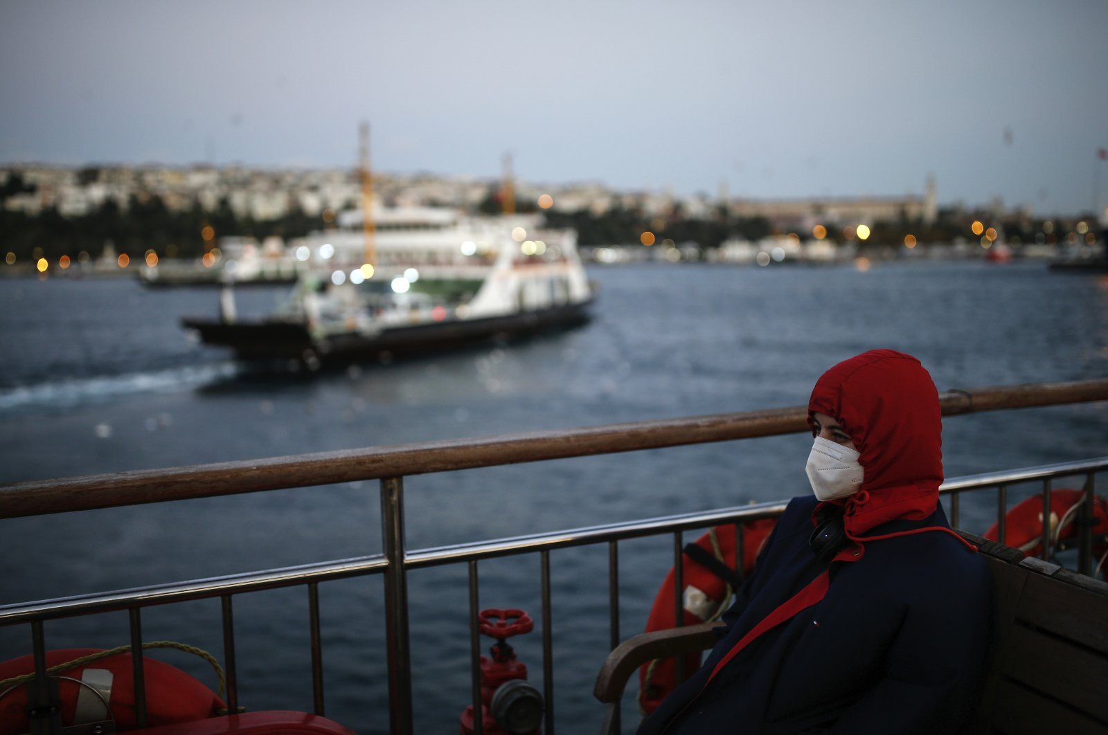 In this Wednesday, Oct. 21, 2020, file photo, a woman, wearing a protective mask to help prevent the spread of the coronavirus, takes a boat trip over the Bosphorus Strait separating the Asian and the European sides of Istanbul. (AP Photo)