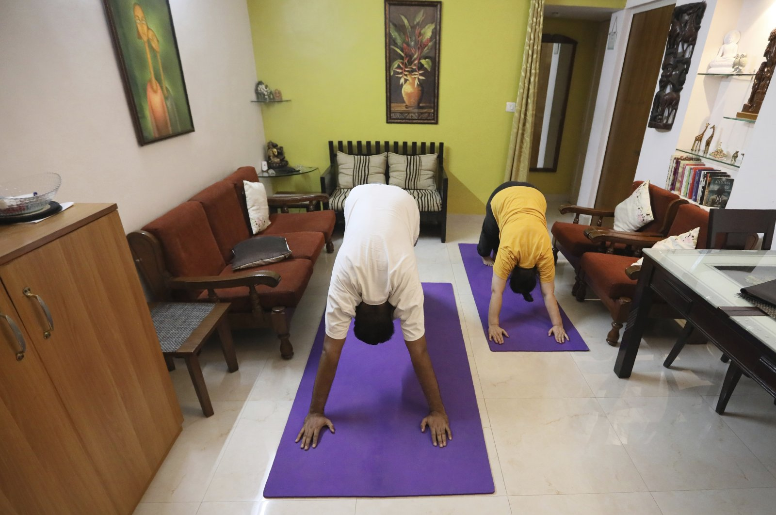 A couple practices yoga in their home to mark International Yoga Day through an online class in New Delhi, India, June 21, 2020. (AP Photo)
