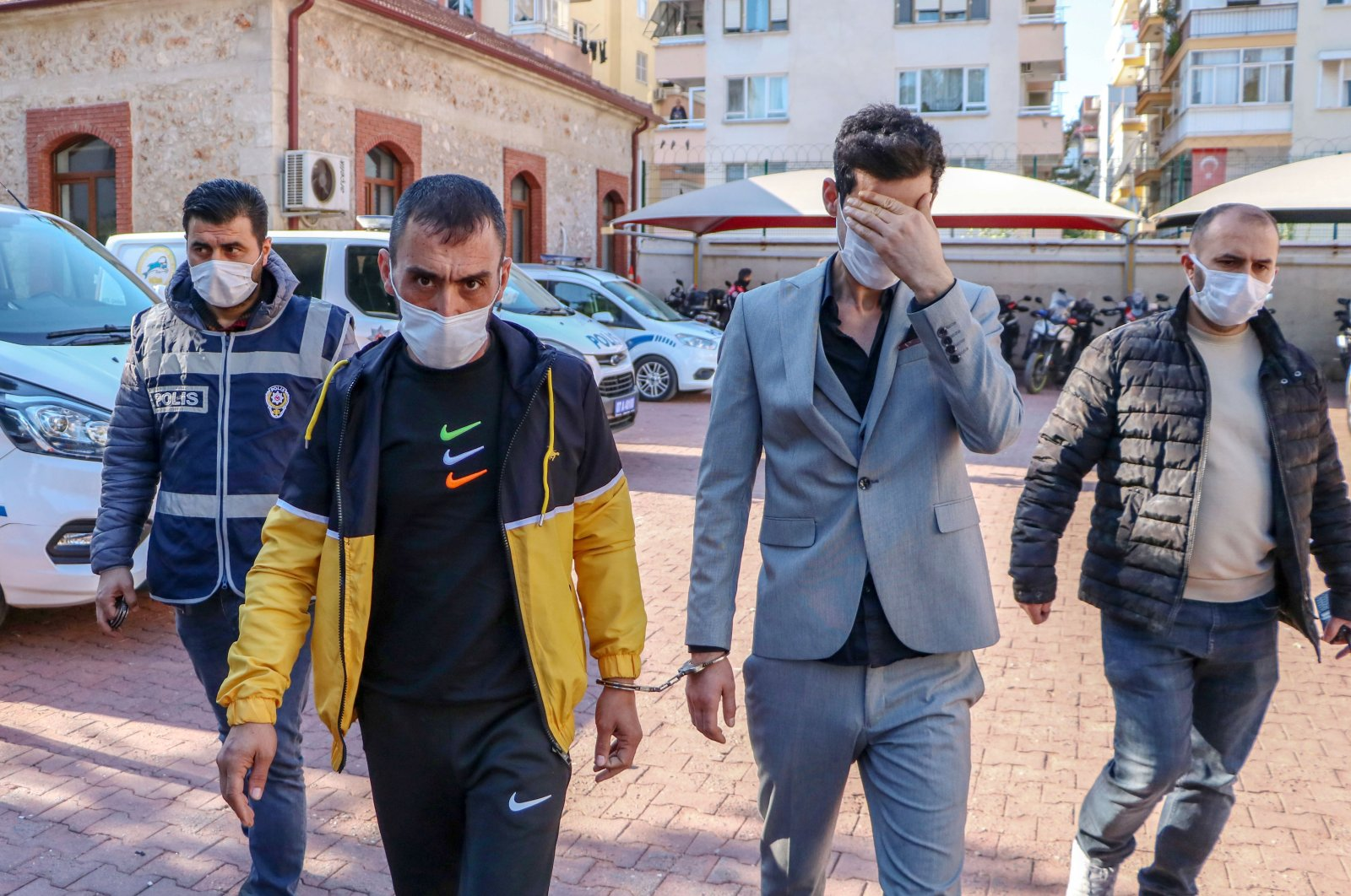 The bridegroom F.A. (L) and his accomplice O.G. head to a police station in the company of officers, in Antalya, southern Turkey, Nov. 29, 2020. (DHA Photo)