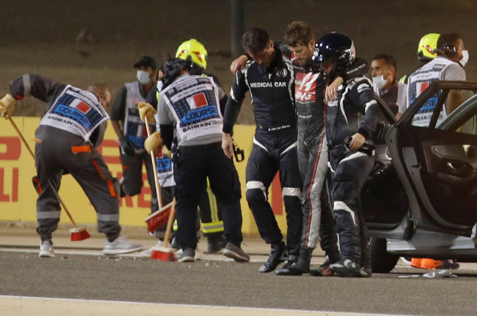 Stewards and medics attend to Romain Grosjean after the crash, in Sakhir, Bahrain, Nov. 29, 2020. (AFP Photo)