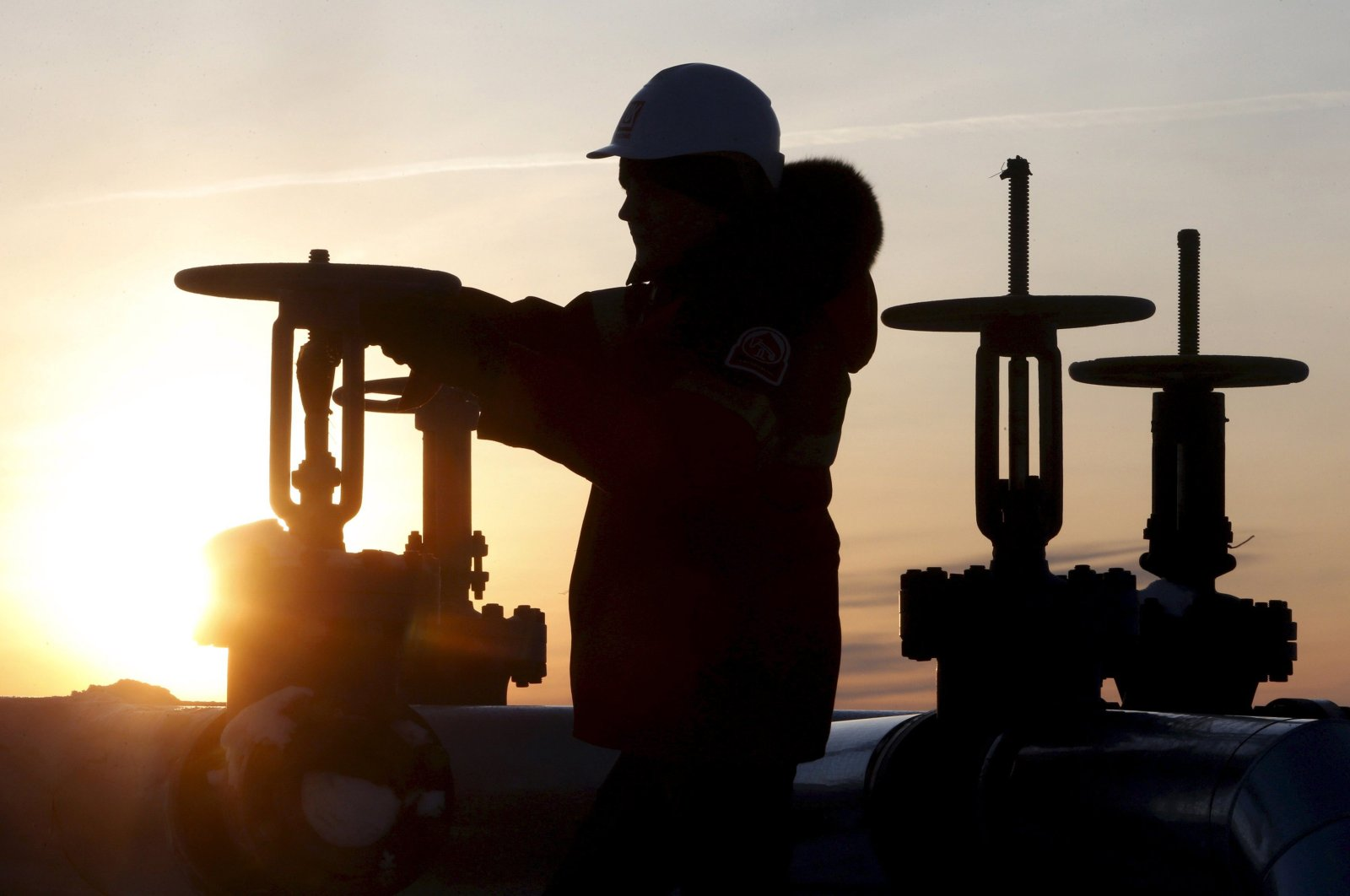 A worker checks the valve of an oil pipe at the Lukoil company-owned Imilorskoye oil field outside the West Siberian city of Kogalym, Russia, Jan. 25, 2016. (Reuters Photo)