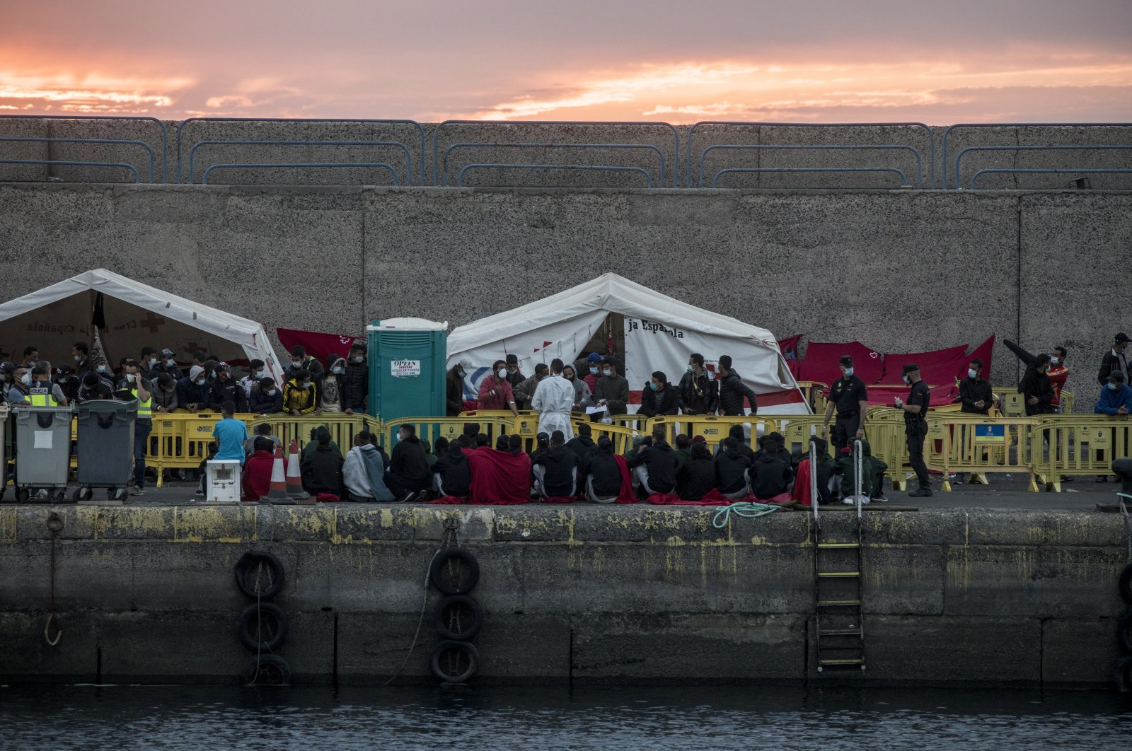 Migrants sit in Arguineguin port after their rescue, Gran Canaria island, Spain, Nov. 24, 2020. (AP Photo)