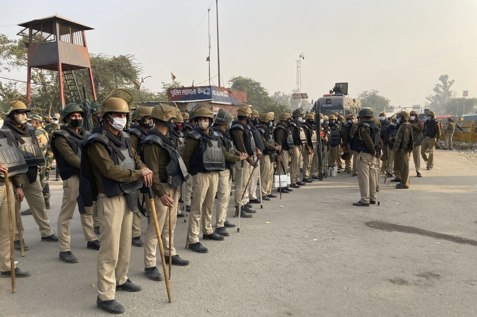 Indian policemen receive a briefing from their officer during a blockade by Indian farmers at the Delhi-Haryana state border, India, Nov. 30, 2020. (AP Photo)