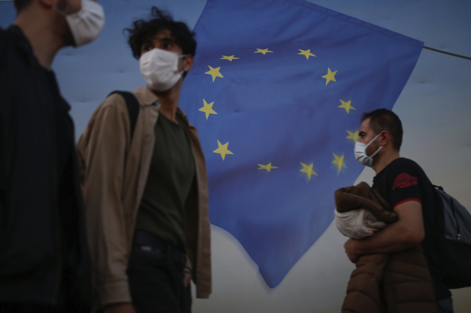 Backdropped by a poster with a European Union flag, people, wearing masks to help protect against the spread of coronavirus, walk in Istanbul, Friday, Oct. 2, 2020. (AP Photo)
