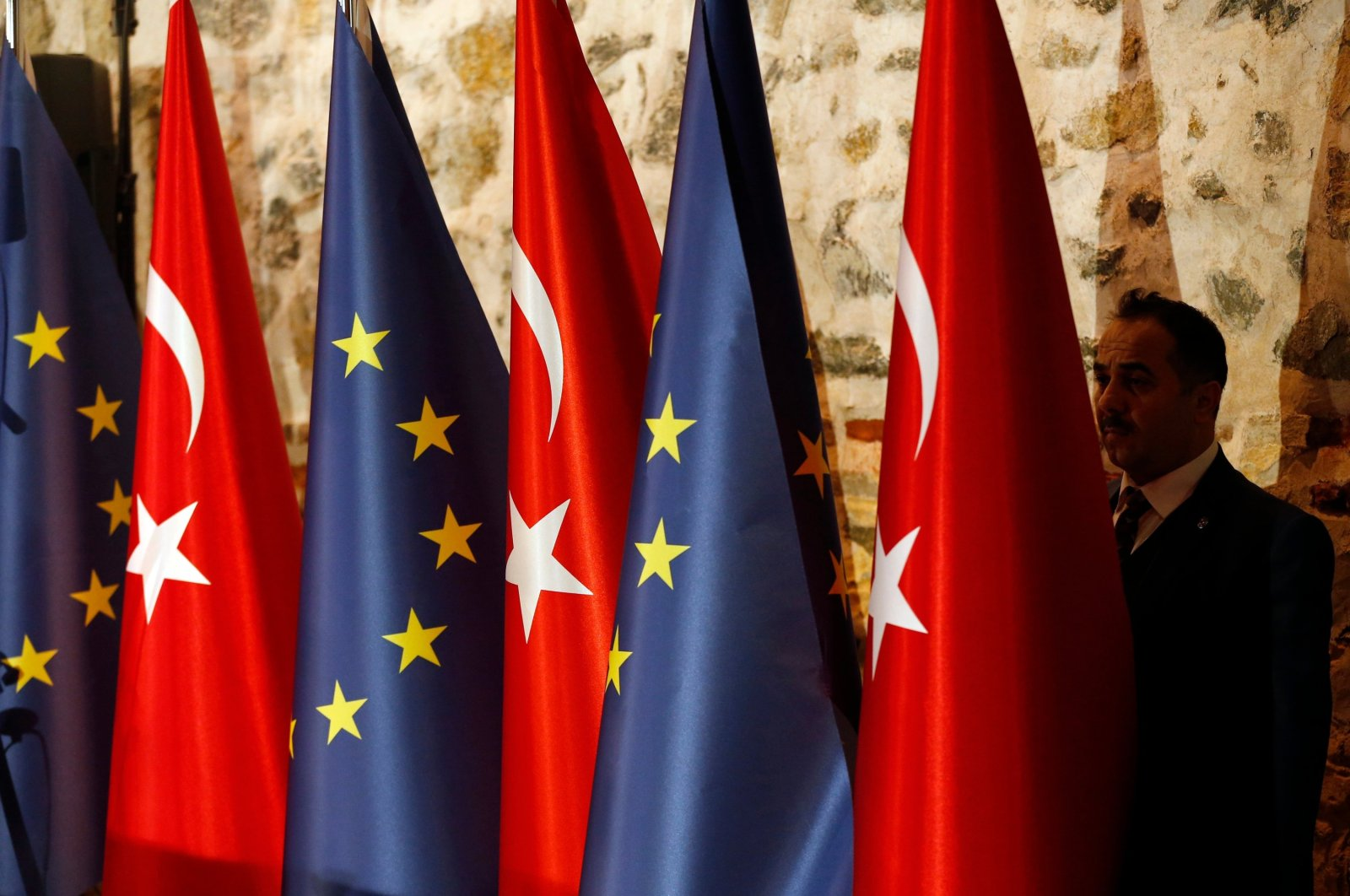 An official adjusts Turkish and European flags prior to the opening session of a high-level meeting between the EU and Turkey, Feb. 28, 2019. (AP)
