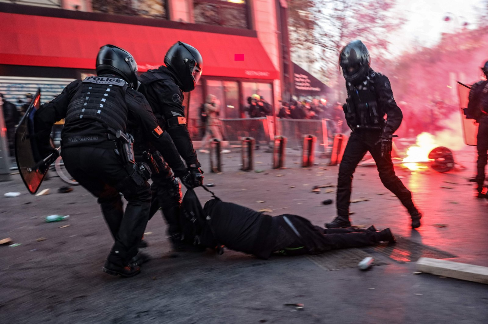 Police officers drag a man on the ground during protests, Paris, Nov. 28, 2020. (AFP Photo)