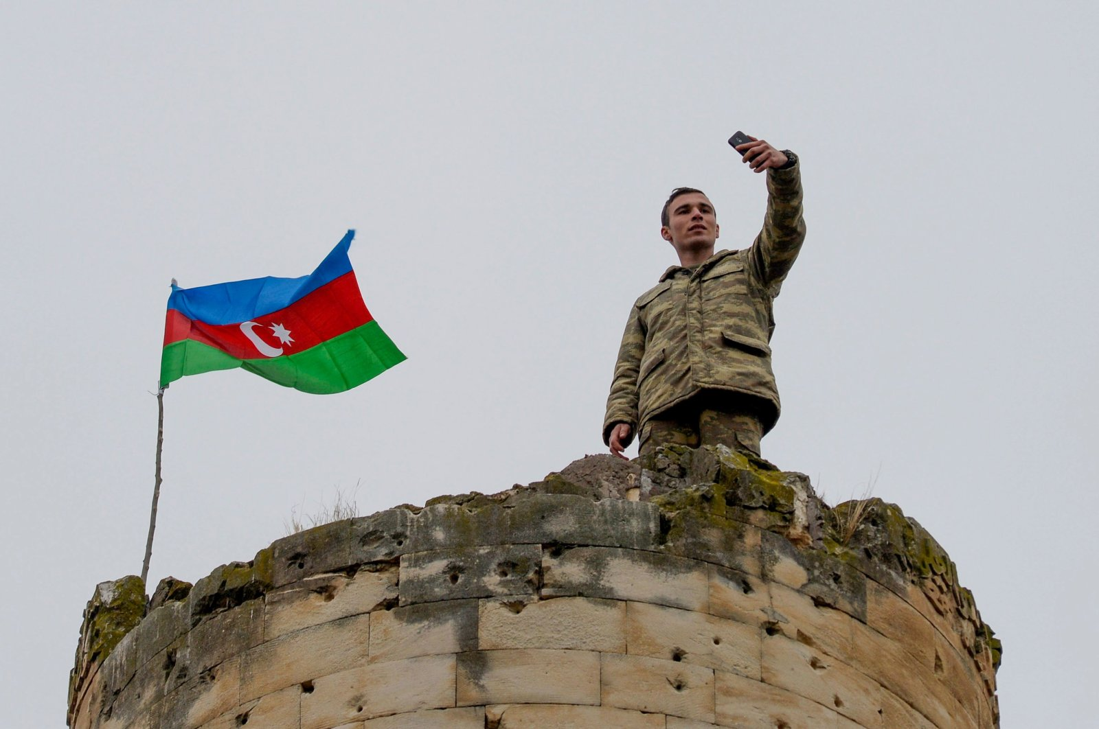 An Azerbaijani soldier takes a selfie with a national flag on the top of a tower outside the town of Fuzuli, Nagorno-Karabakh, Nov. 26, 2020. (AFP File Photo)