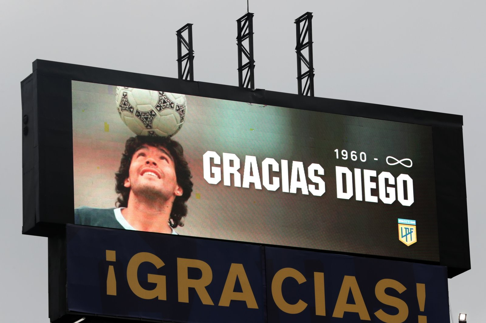 """A screen displays an image of Diego Maradona with the message """"1960-infinity Thanks Diego"""" as a tribute, Nov. 29, 2020. (REUTERS)"""