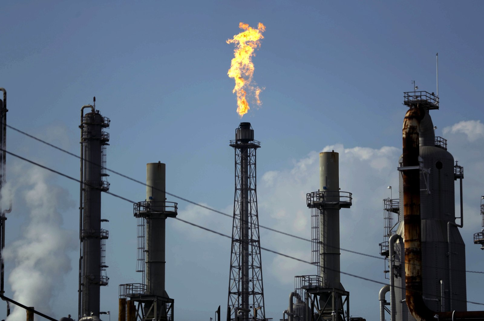 A flame burns at the Shell Deer Park oil refinery in Deer Park, Texas, Aug. 31, 2017. With the viral outbreak spreading to more countries, the price of oil has dropped precipitously as global demand weakens even further. That has sent shares tumbling for oil giants like Exxon and Chevron while smaller producers with idling rigs continue to slash jobs. (AP Photo)