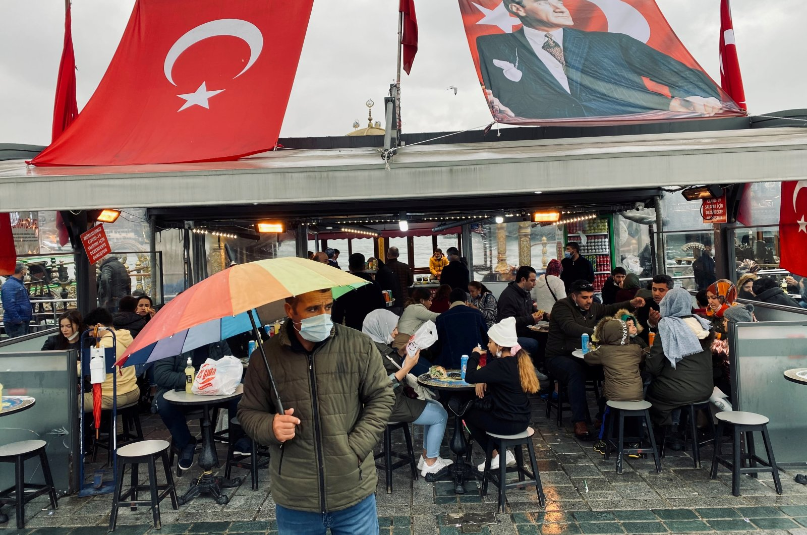 A man wearing a protective mask stands in front of a fish and bread restaurant, amid the coronavirus outbreak, in Istanbul, Turkey, Nov. 7, 2020. (Reuters Photo)