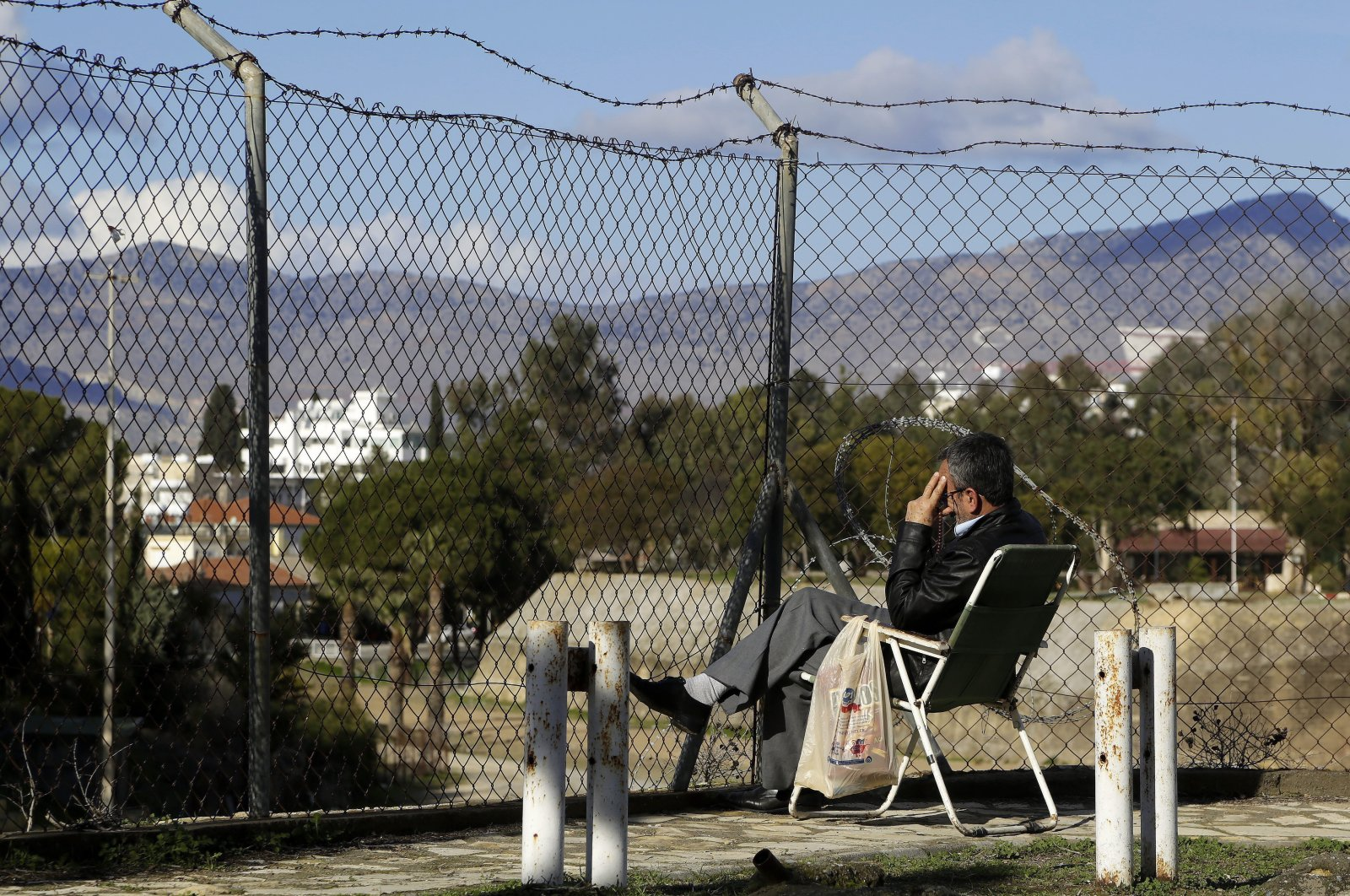 A man sits in front of the fence that divides the Turkish and Greek parts of the island of Cyprus, as he watches from the Turkish Republic of Northern Cyprus' (TRNC) capital Lefkoşa (Nicosia), Jan. 11, 2017. (AP Photo)
