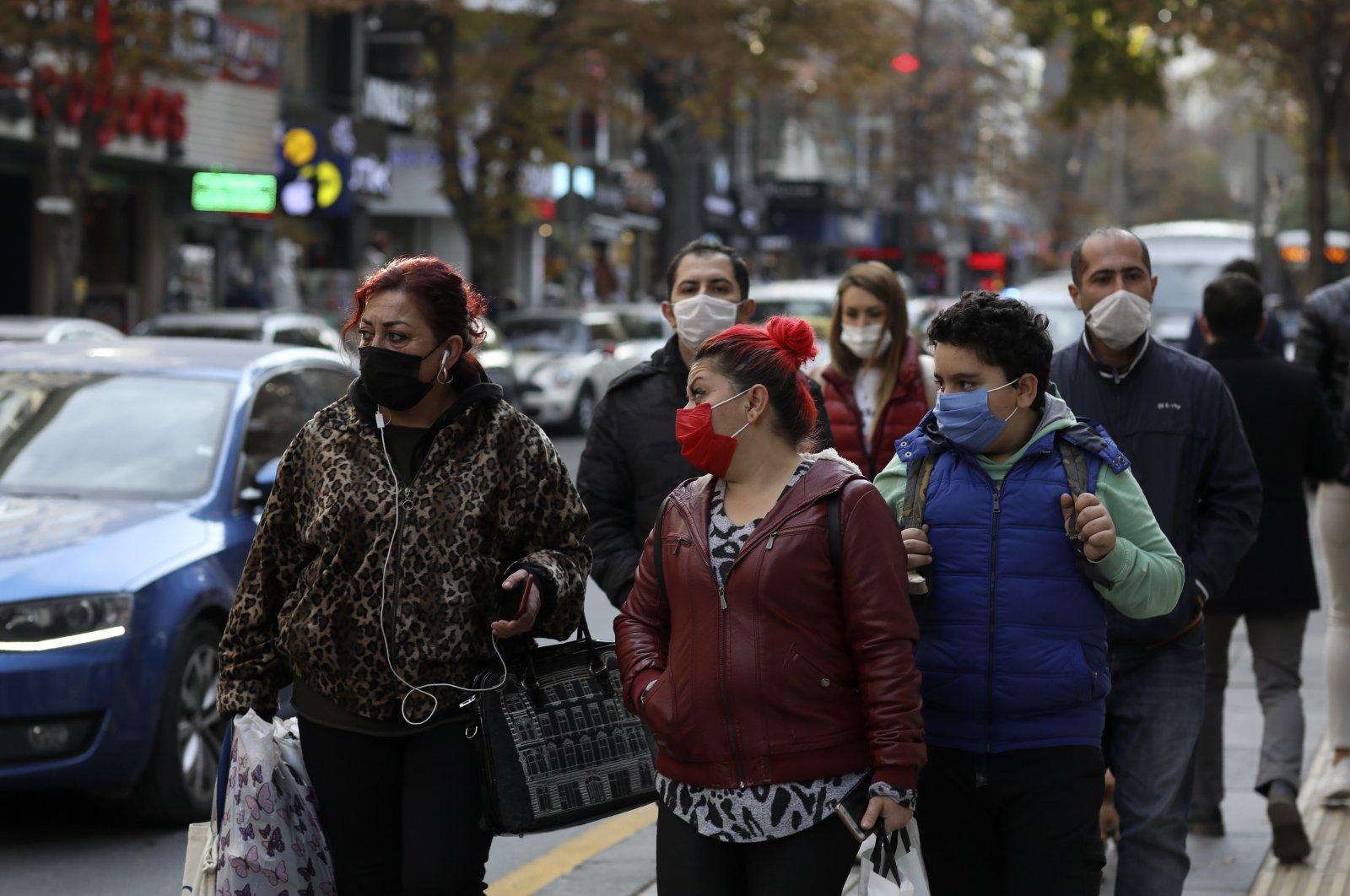 People wearing protective masks walk on a street in the capital Ankara, Turkey, Nov. 30, 2020. (AP Photo)