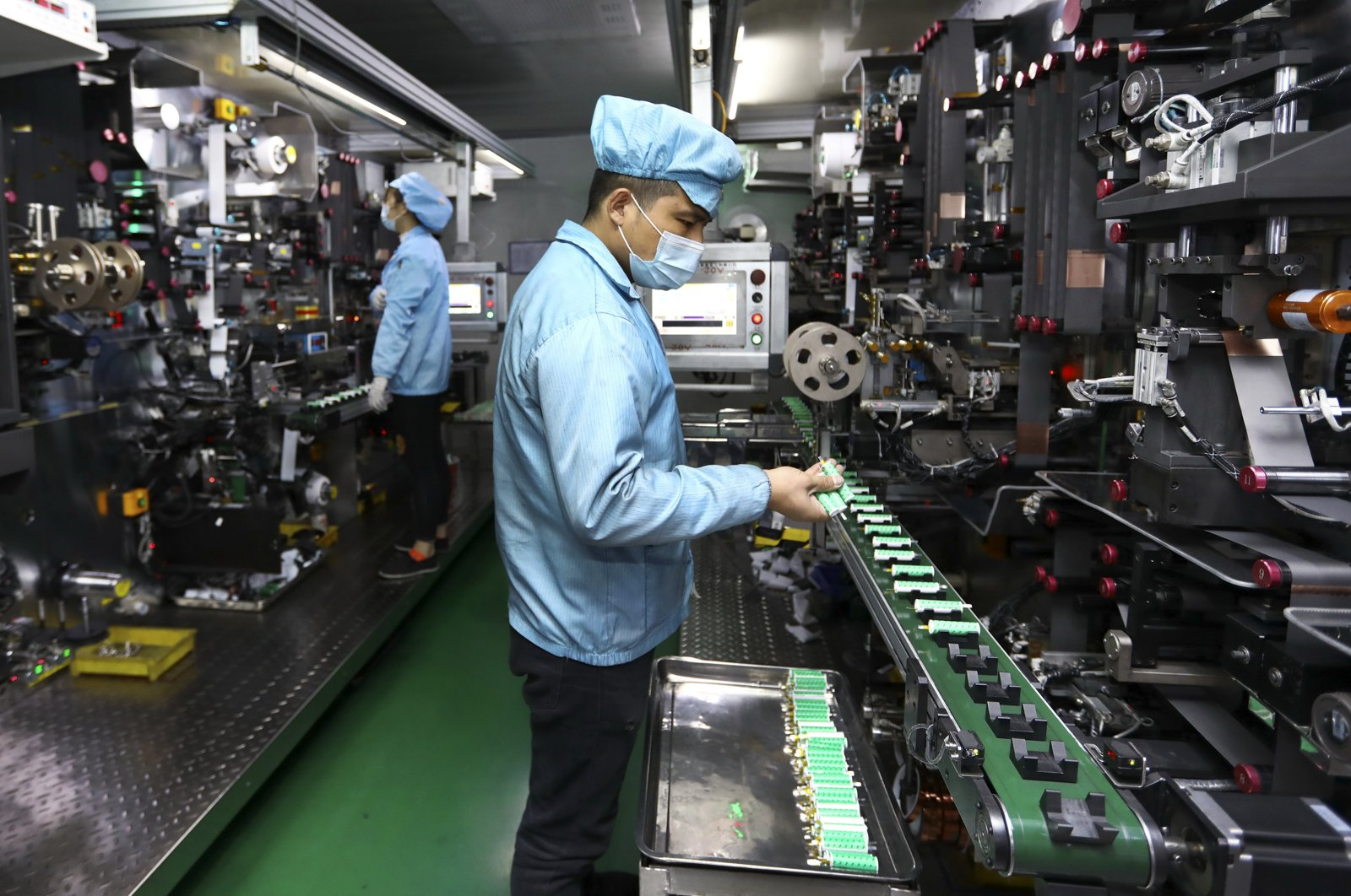 Workers place batteries on a machine at a factory manufacturing lithium batteries in Huaibei in central China's Anhui province, Nov. 14, 2020. (Chinatopix via AP)