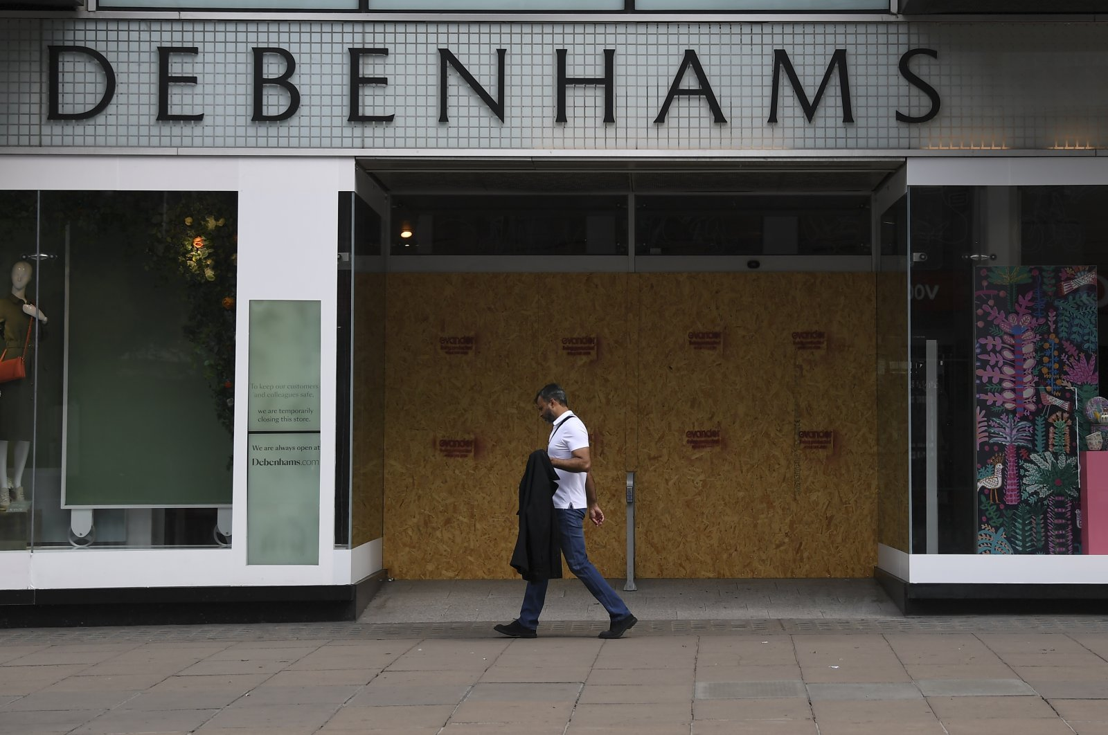 A man walks past a Debenhams store in the main shopping street Oxford Street, London, U.K., June 12, 2020. (AP Photo)