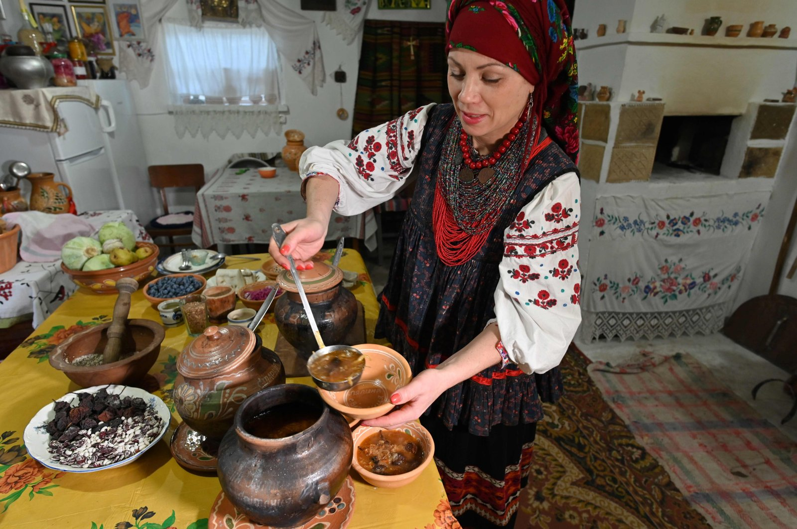 An Ukrainian ethnologist and historian, who studies borscht and has 365 of its unique recipes from all over Ukraine in her private collection, wears Ukraine's traditional clothes and headdress cooks borscht in clay pots in the wood stove in the village of Opishnya in Poltava region, Nov. 26, 2020. (AFP Photo)
