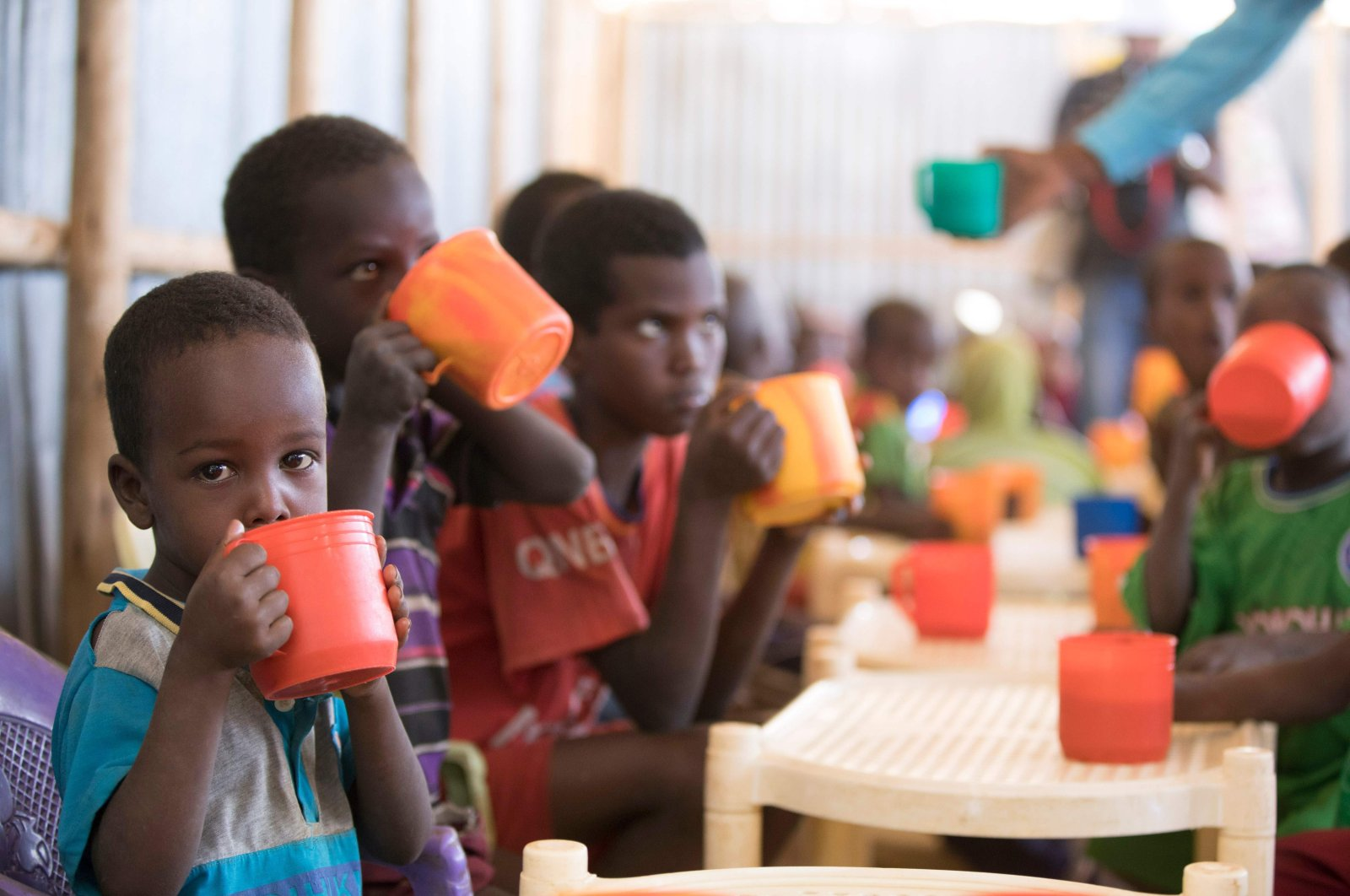 Young children drink a high protein mix provided by the World Food Programme (WFP) at Mekladida refugee camp in the Somali region of Ethiopia, Dec. 1, 2020. (AFP Photo)
