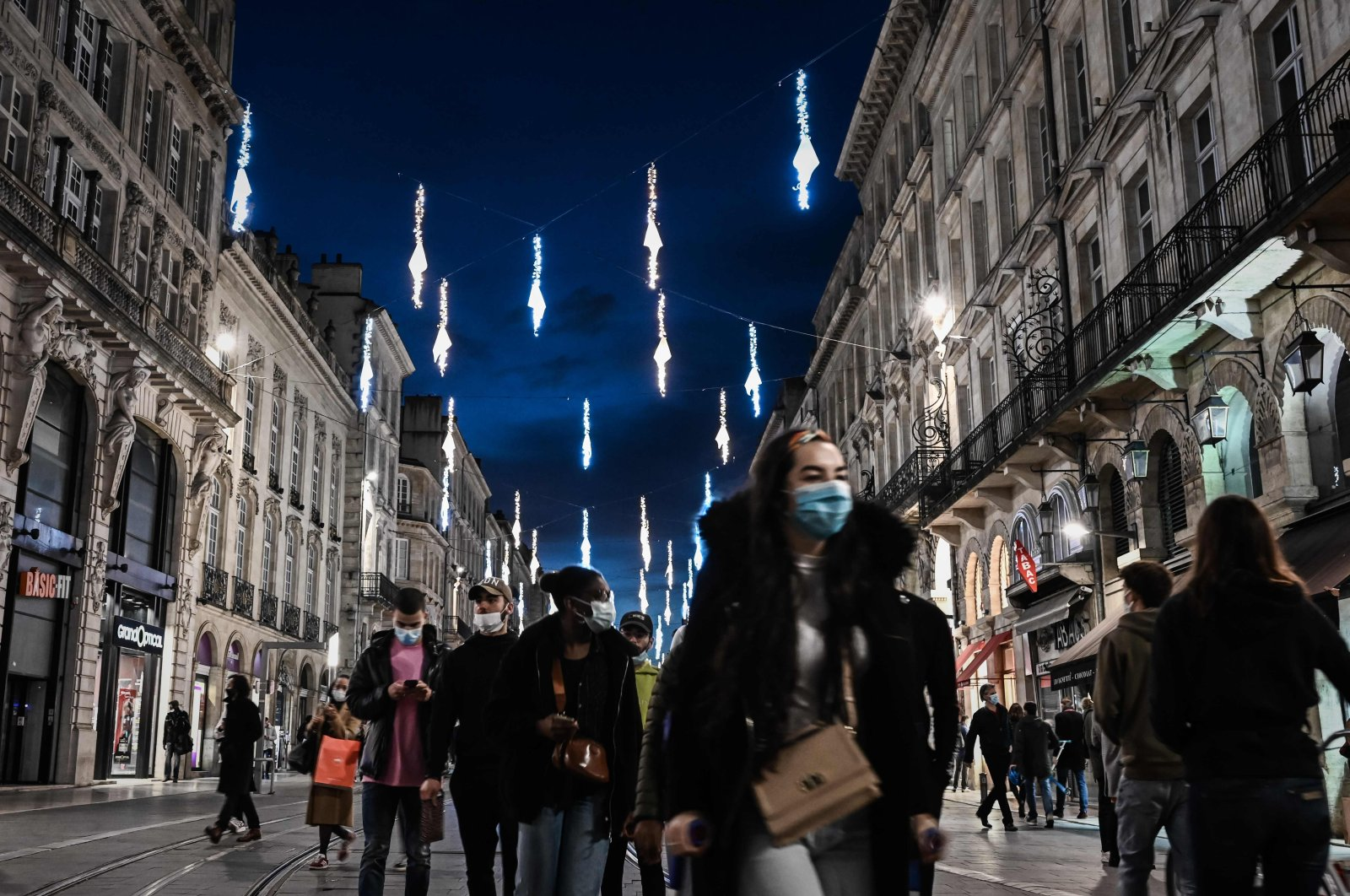 Pedestrians walk under Christmas decorations in a shopping street in Bordeaux, southwestern France, Nov. 28, 2020. (AFP Photo)
