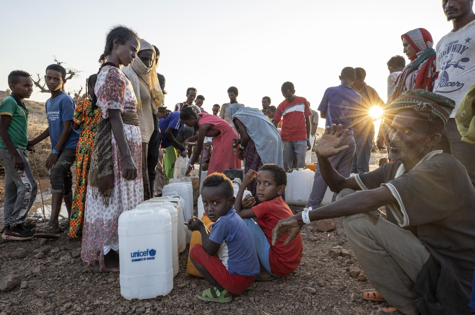 Tigray women and men who fled the conflict in Ethiopia's Tigray region, wait in line to pour water into gallons, at Umm Rakouba refugee camp in Qadarif, eastern Sudan, Friday, Nov. 27, 2020. (AP Photo)