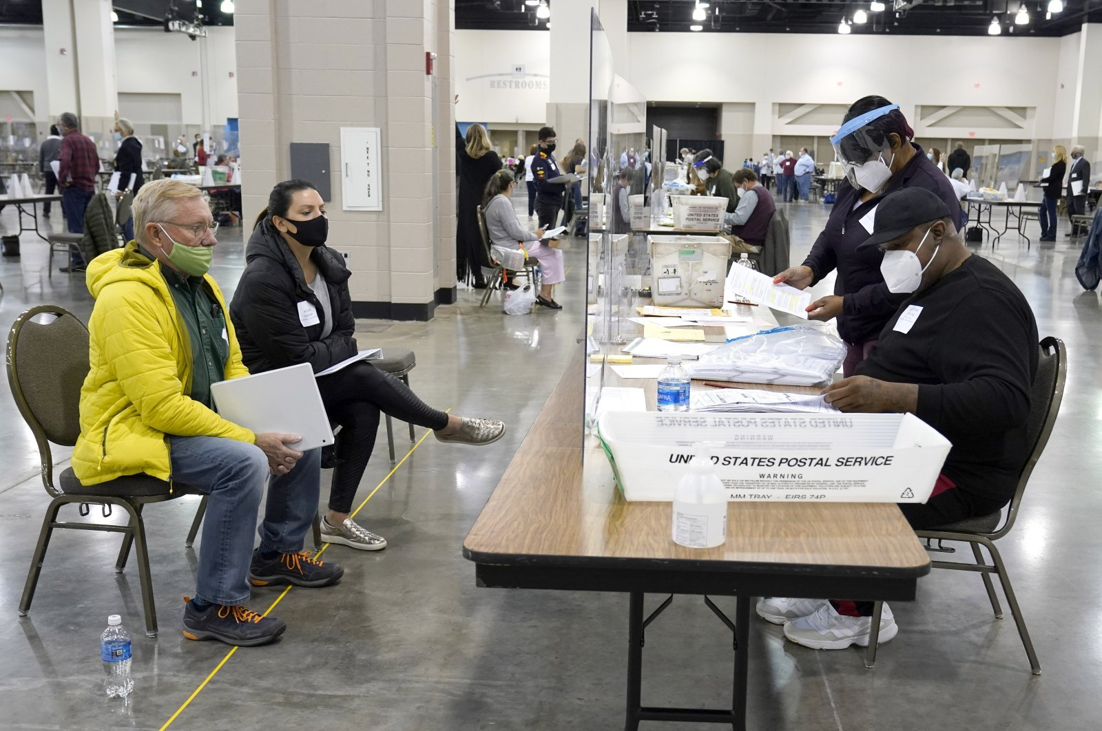 Election workers, right, verify ballots as recount observers, left, watch during a Milwaukee hand recount of presidential votes at the Wisconsin Center in Milwaukee, U.S., Nov. 20, 2020. (AP Photo)