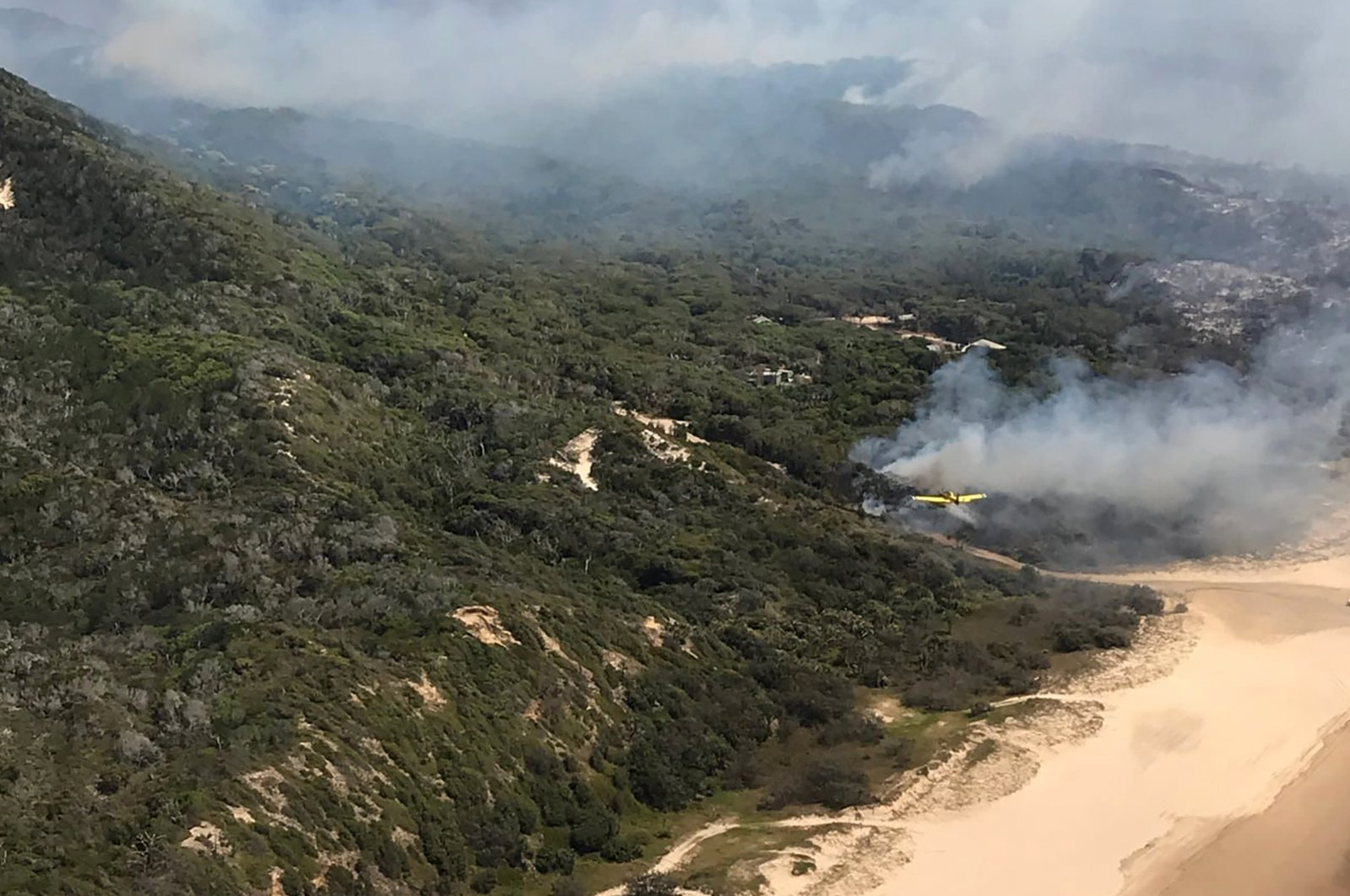 Smoke blows over hills and toward the ocean at Fraser Island, Australia, Dec. 2, 2020. (Queensland Fire and Emergency Services via AP)