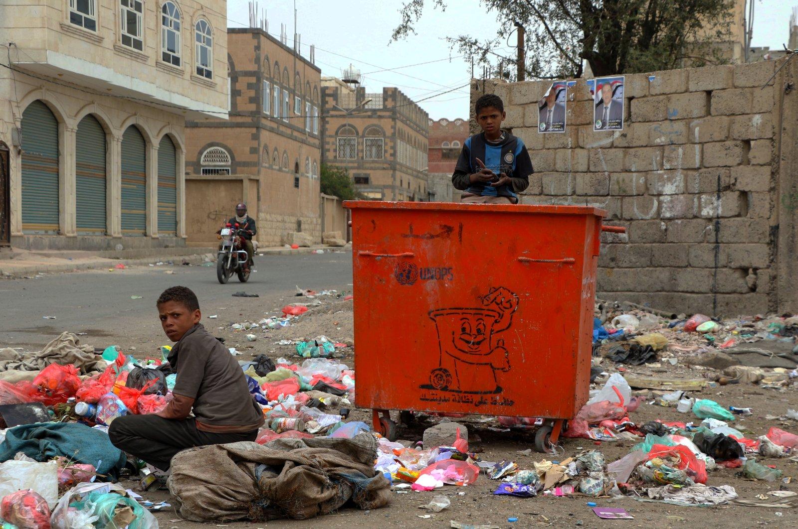 Two Yemeni children search for food from public garbage inSanaa, Yemen, Nov. 25, 2020. (AA Photo)