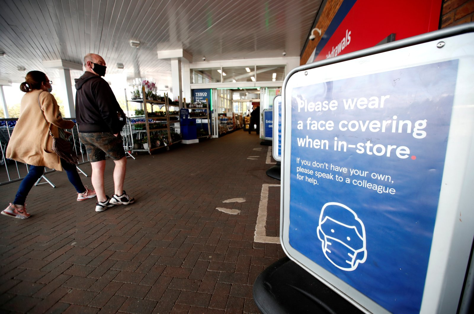 A sign requests people to wear masks at the entrance to a Tesco supermarket in Hatfield, the U.K., Oct. 6, 2020. (Reuters Photo)