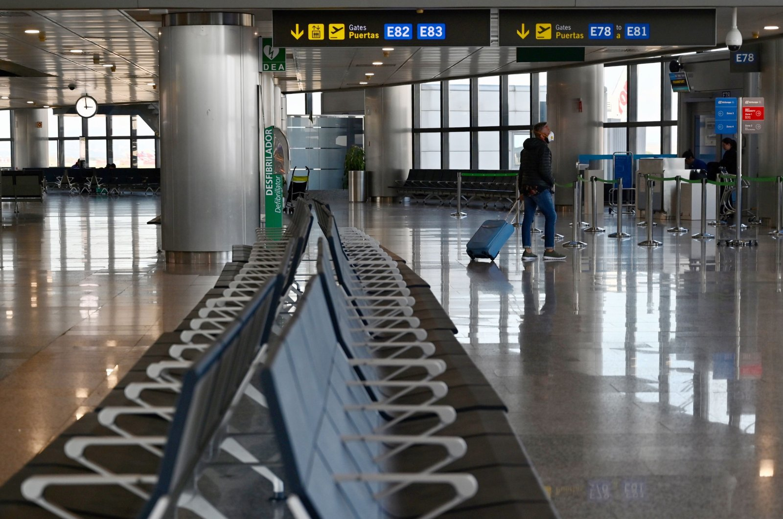 A person wearing a protective mask pulls a trolley along rows of empty seats at the Madrid-Barajas Adolfo Suarez Airport in Barajas on March 14, 2020. (AFP Photo)