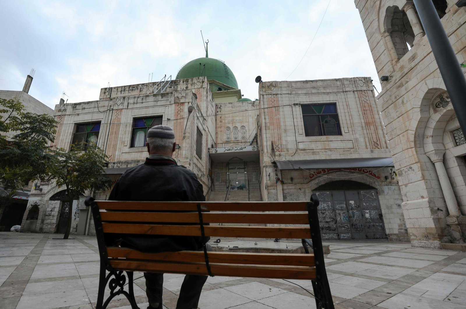 A Palestinian man sits on a bench on an empty street, as Palestinian authorities have announced a lockdown on weekends to curb the spread of COVID-19, in the occupied West Bank city of Nablus, Palestine, Nov. 27, 2020. (AFP Photo)