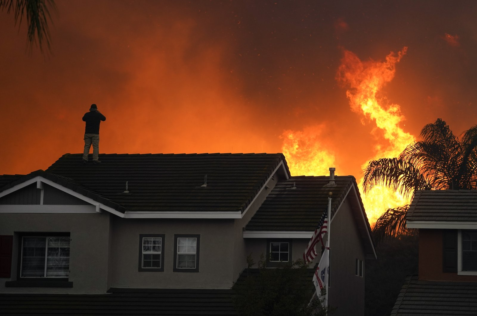 A man stands on the roof of his home as the Blue Ridge Fire burns along the hillside in Chino Hills, California, U.S., Oct. 27, 2020. (AP Photo)