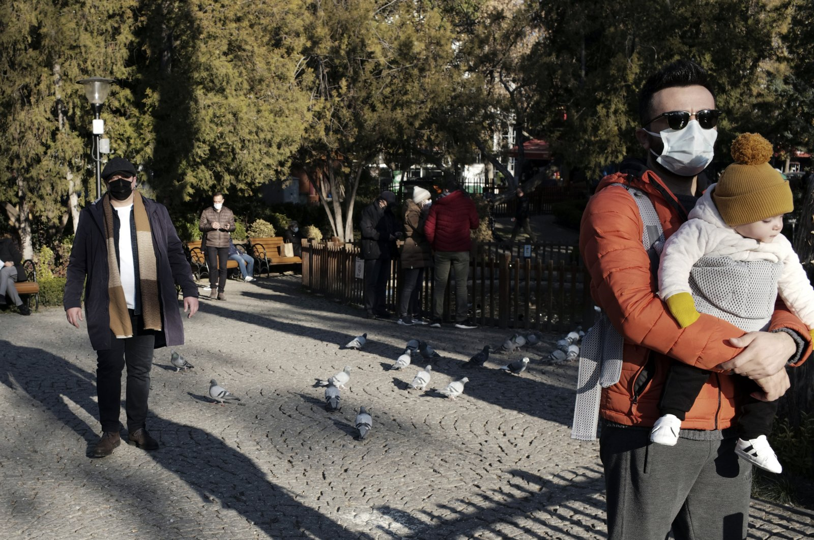 People wearing masks to help protect against the spread of coronavirus, visit a public garden in the capital Ankara, Turkey, Nov. 27, 2020. (AP Photo)