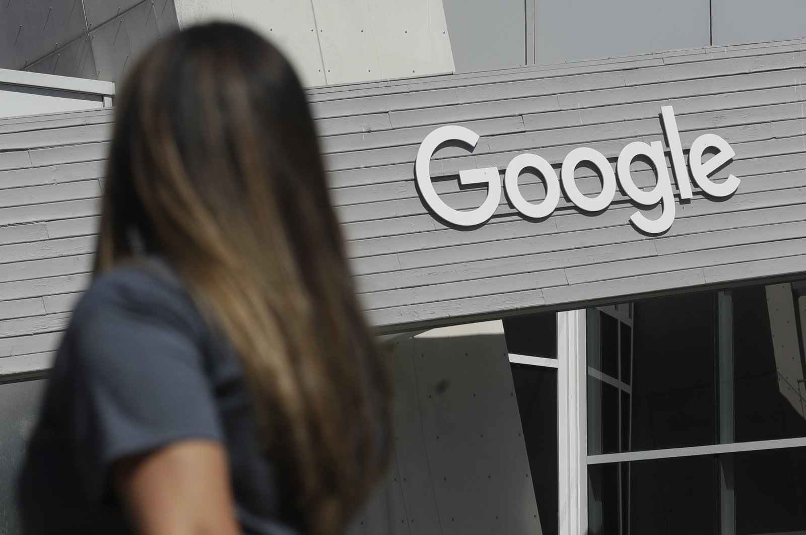 A woman walks below a Google sign on the campus in Mountain View, California, Sept. 24, 2019. (AP Photo)