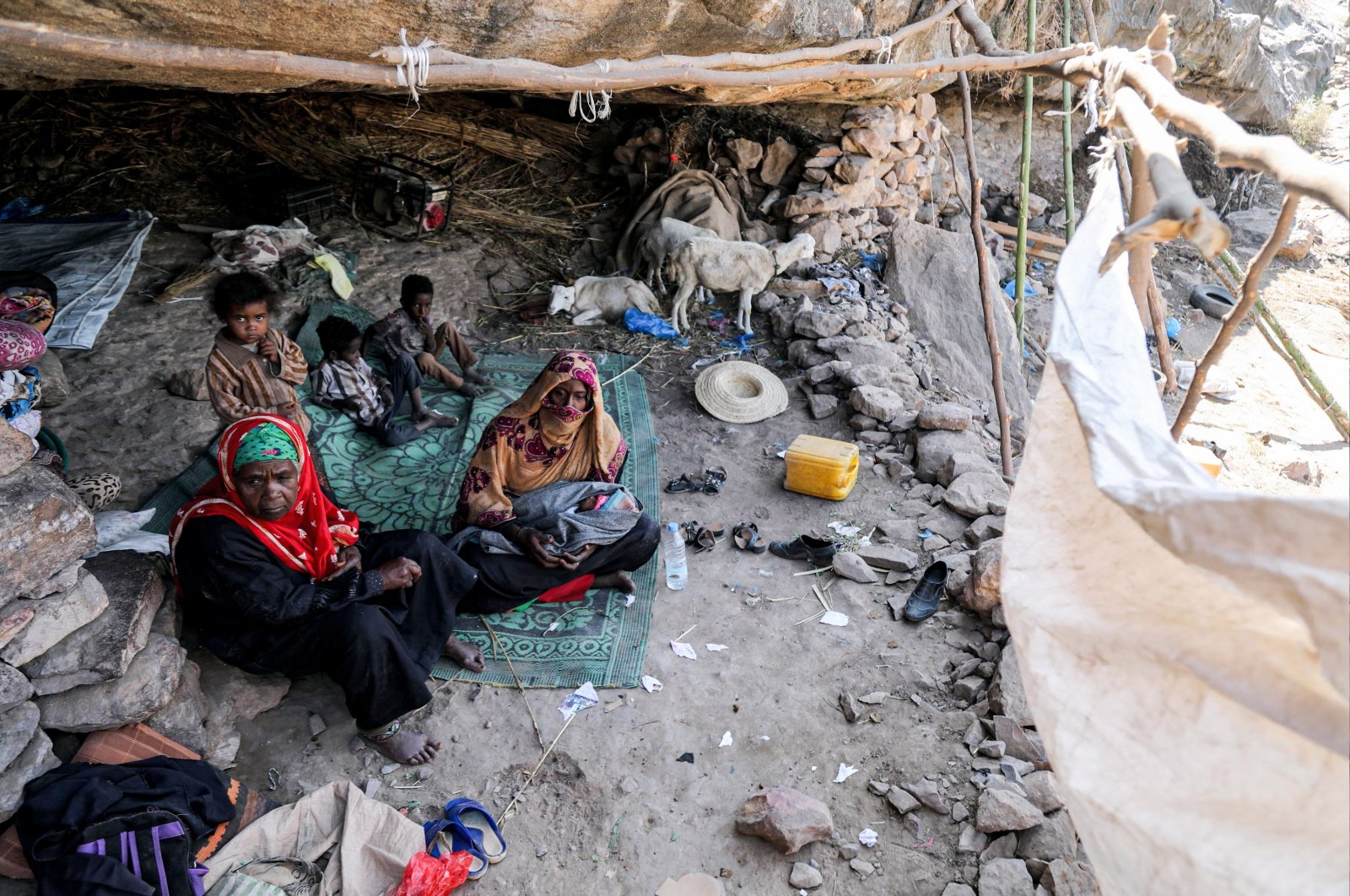 Women and children sit on the ground in a shack by a cave where a Yemeni family has sought refuge due to poverty and lack of housing, west of the suburbs of Taez, Yemen, Dec. 2, 2020. (AFP Photo)