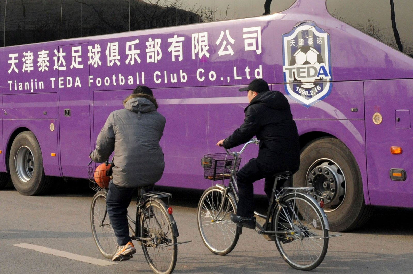 Two men ride past a Tianjin TEDA football club bus on a road in Tianjin, China, Feb. 19, 2013. (AFP Photo)