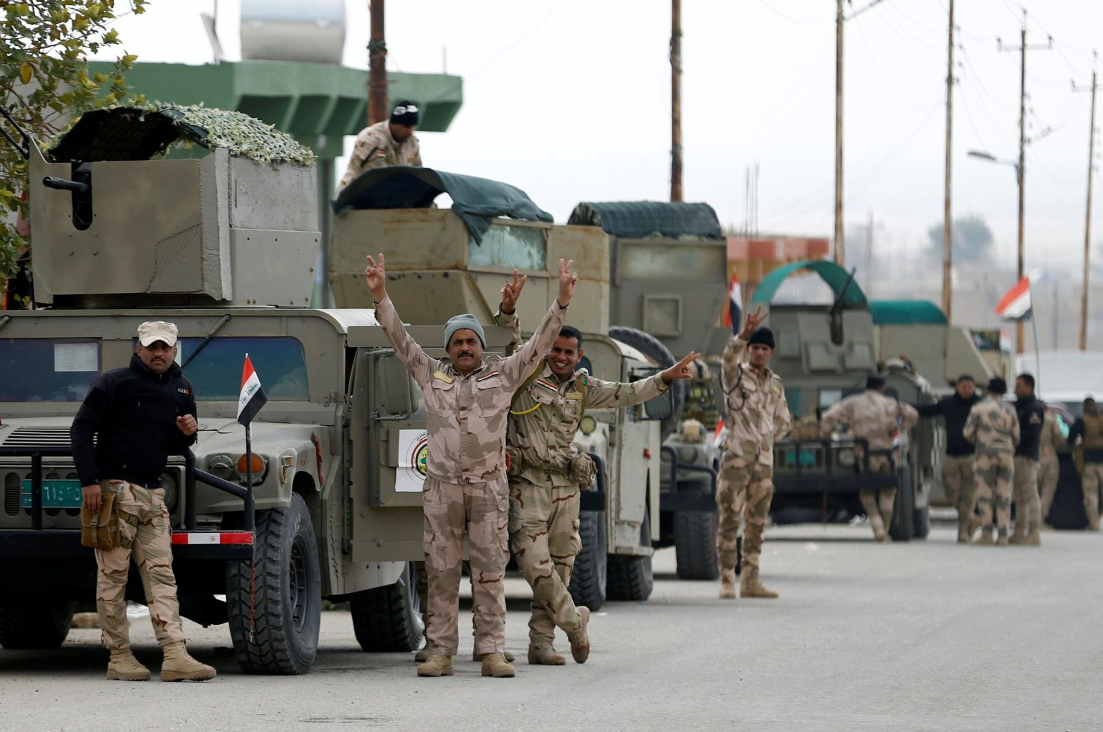 Members of Iraqi security forces flash a victory sign during deployments in Sinjar, Iraq, Dec. 1, 2020. REUTERS
