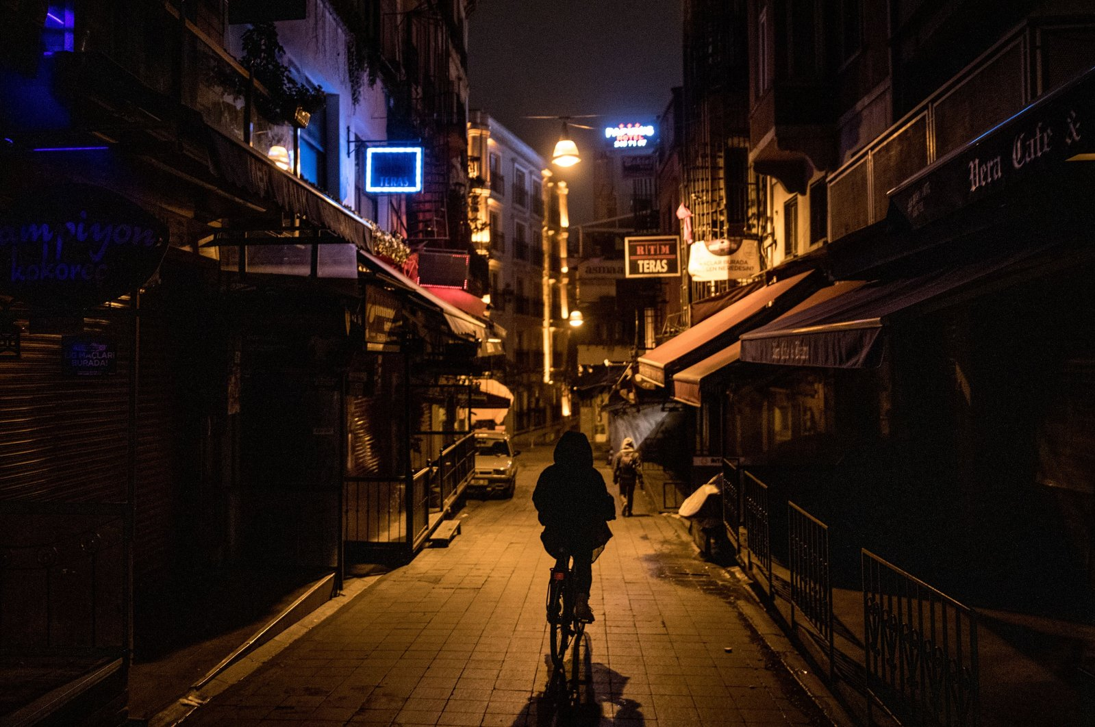 A man rides a bike down a near-empty restaurant street as a new weekday curfew comes into effect in Istanbul, Dec. 1, 2020.  (Photo by Getty Images)