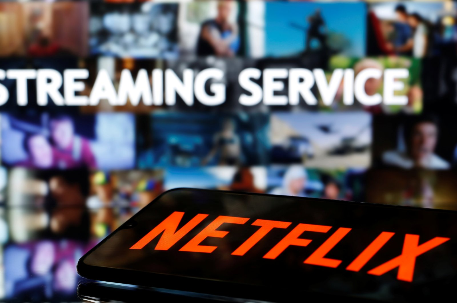 "A smartphone with the Netflix logo lies in front of displayed ""Streaming service"" words in this illustration taken on March 24, 2020. (Reuters Photo)"