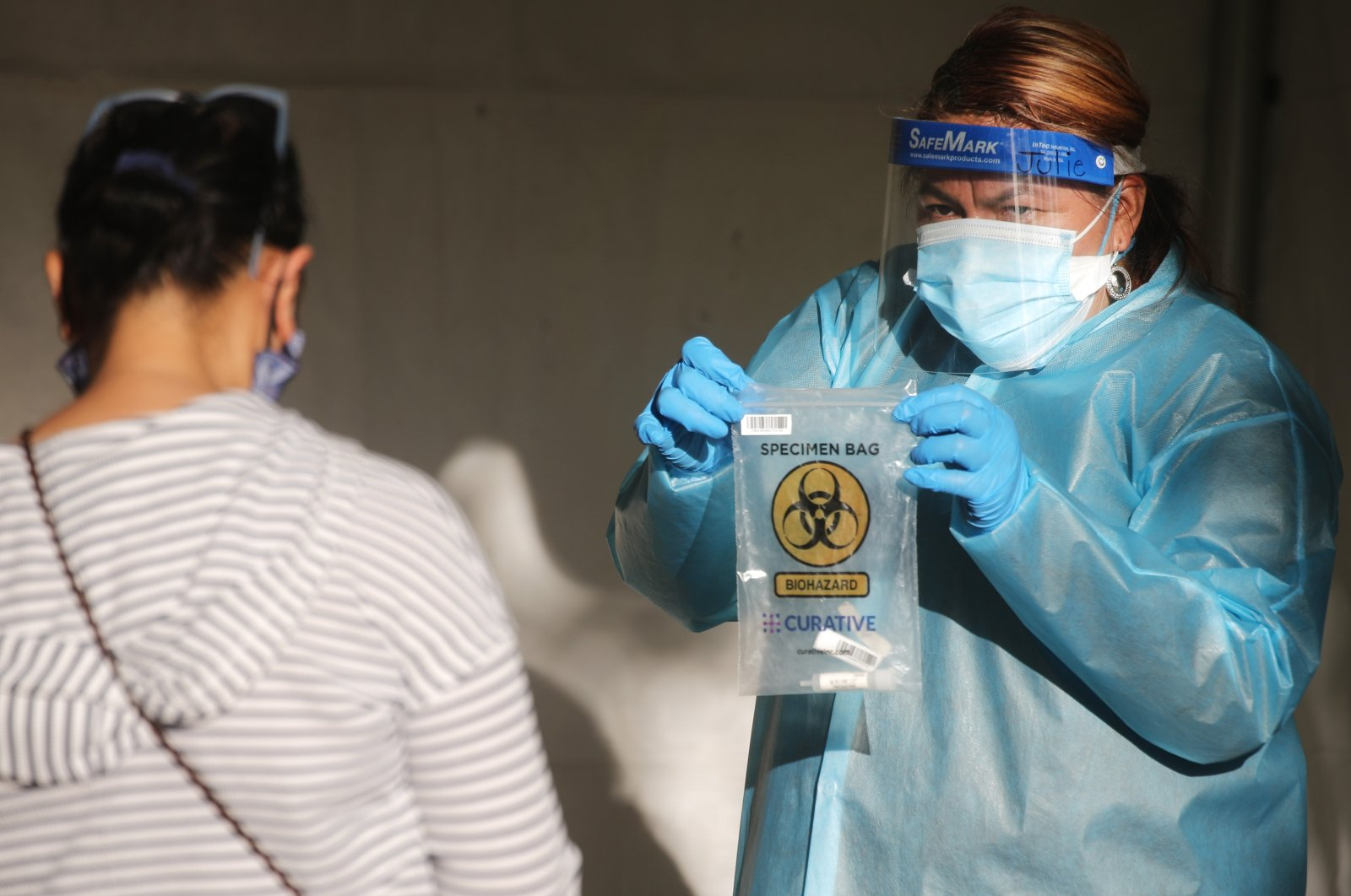 A health care worker holds a specimen bag at a walk-up COVID-19 testing site, San Fernando, California, Dec. 2, 2020. (AFP Photo)