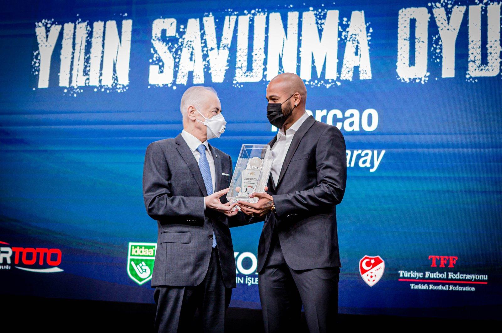 Galatasaray chairperson Mustafa Cengiz gives an award to Galatasaray defender Marcao, in Istanbul, Turkey, Dec. 3, 2020. (Photo by Hatice Çınar)
