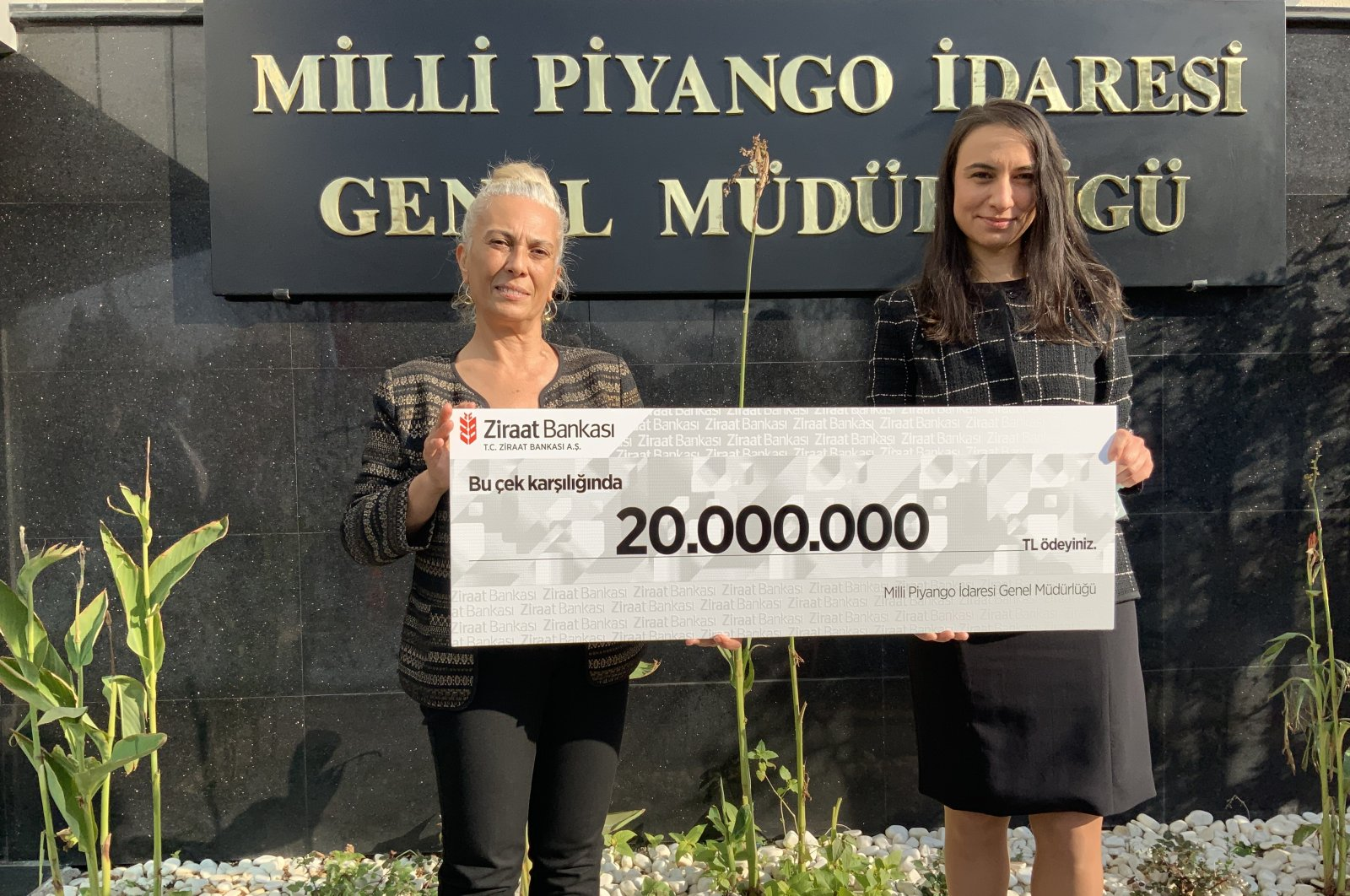 A National Lottery representative and a Ziraat Bank employee who received the prize on behalf of an anonymous winner, pose with a symbolic check for the prize, in the capital Ankara, Turkey, Dec. 3, 2020. (AA PHOTO)