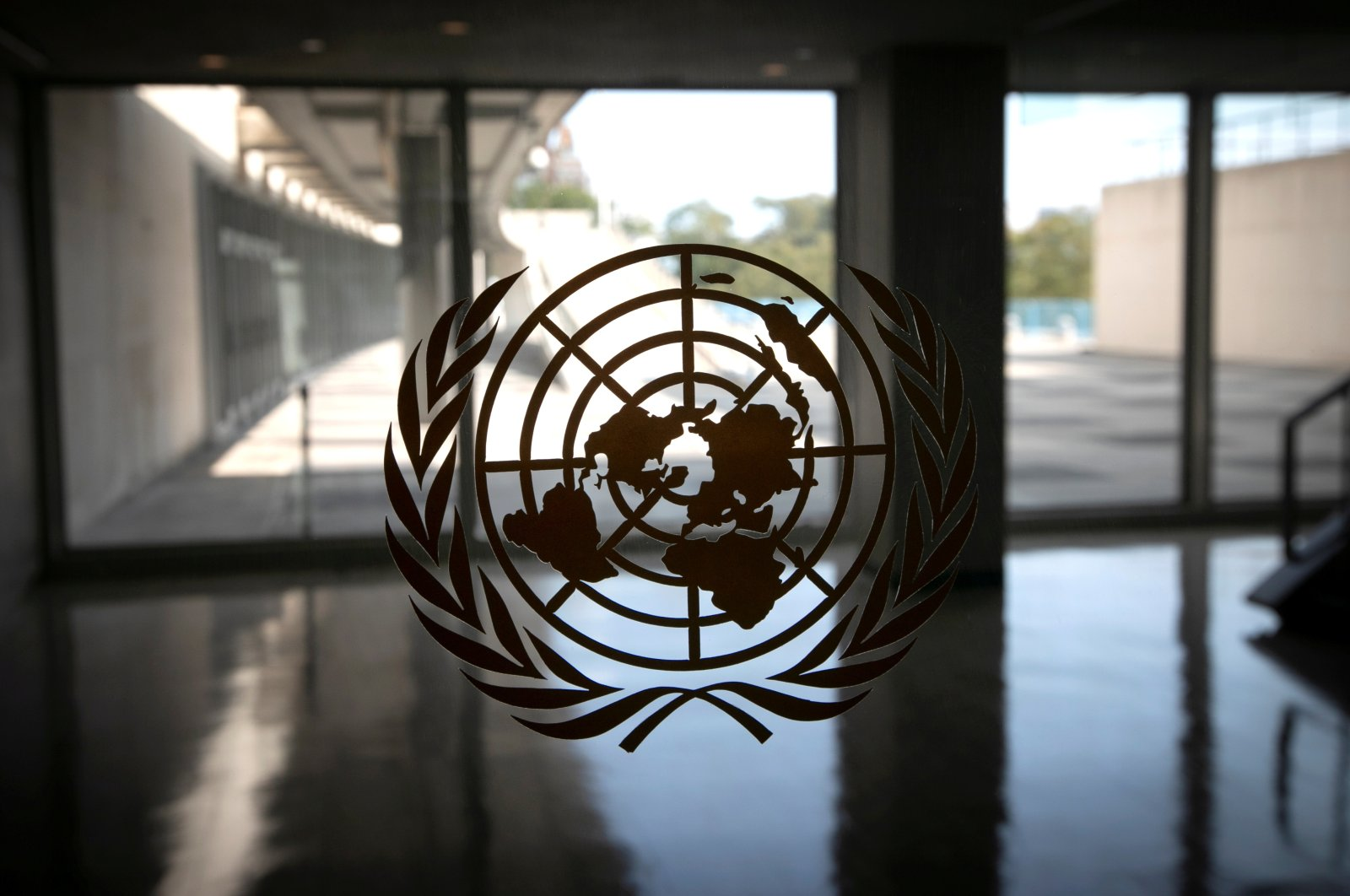 The United Nations logo is seen on a window in an empty hallway at U.N. headquarters in New York, U.S., Sept. 21, 2020. (REUTERS Photo)