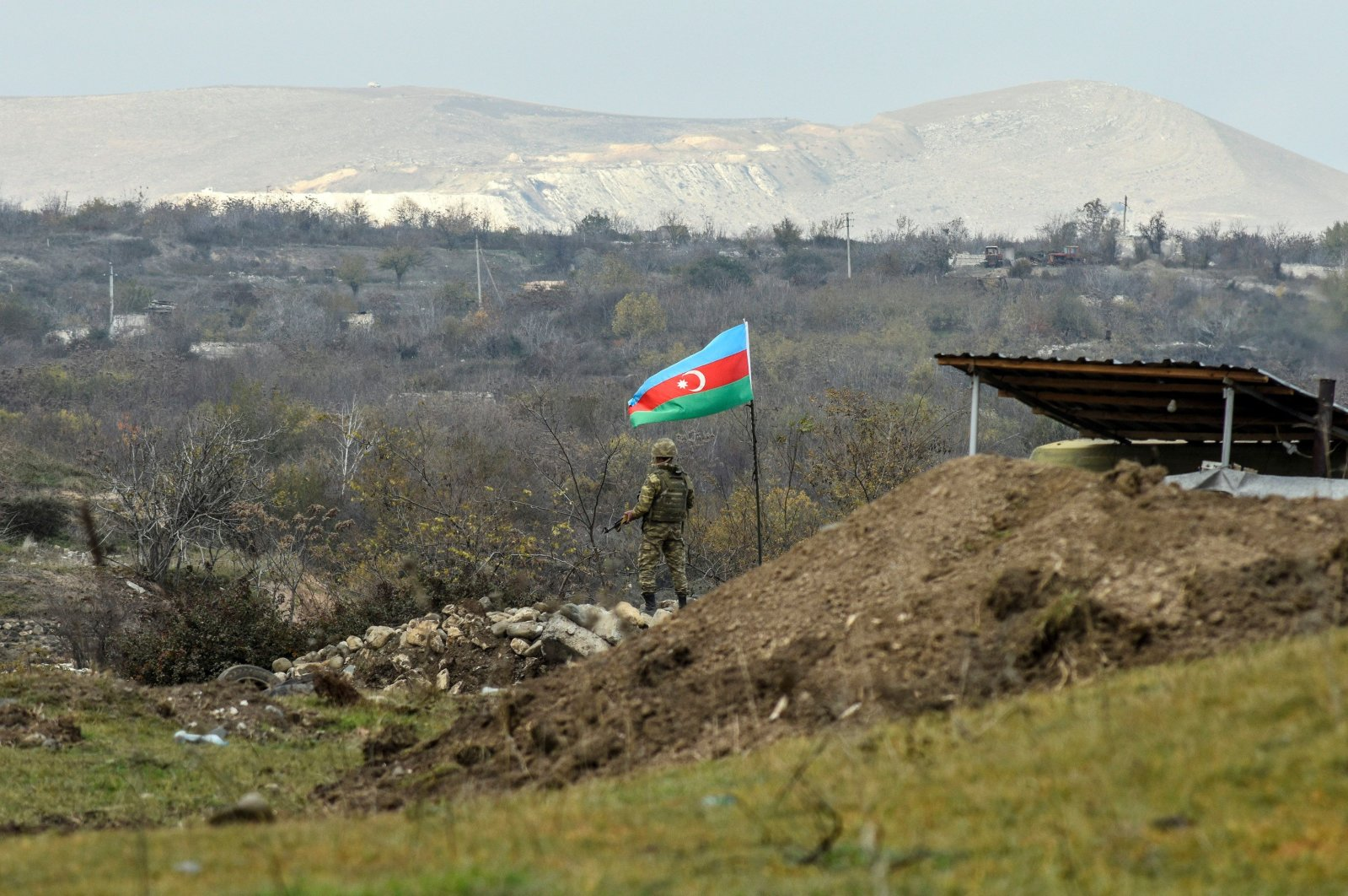 An Azerbaijani soldier stands guard at a checkpoint on a road entering Fuzuli from Hadrut a day after Baku's army entered the final district given up by Armenia under a peace deal that ended weeks of fighting over the Nagorno-Karabakh region, Azerbaijan, Dec. 2, 2020. (AFP Photo)
