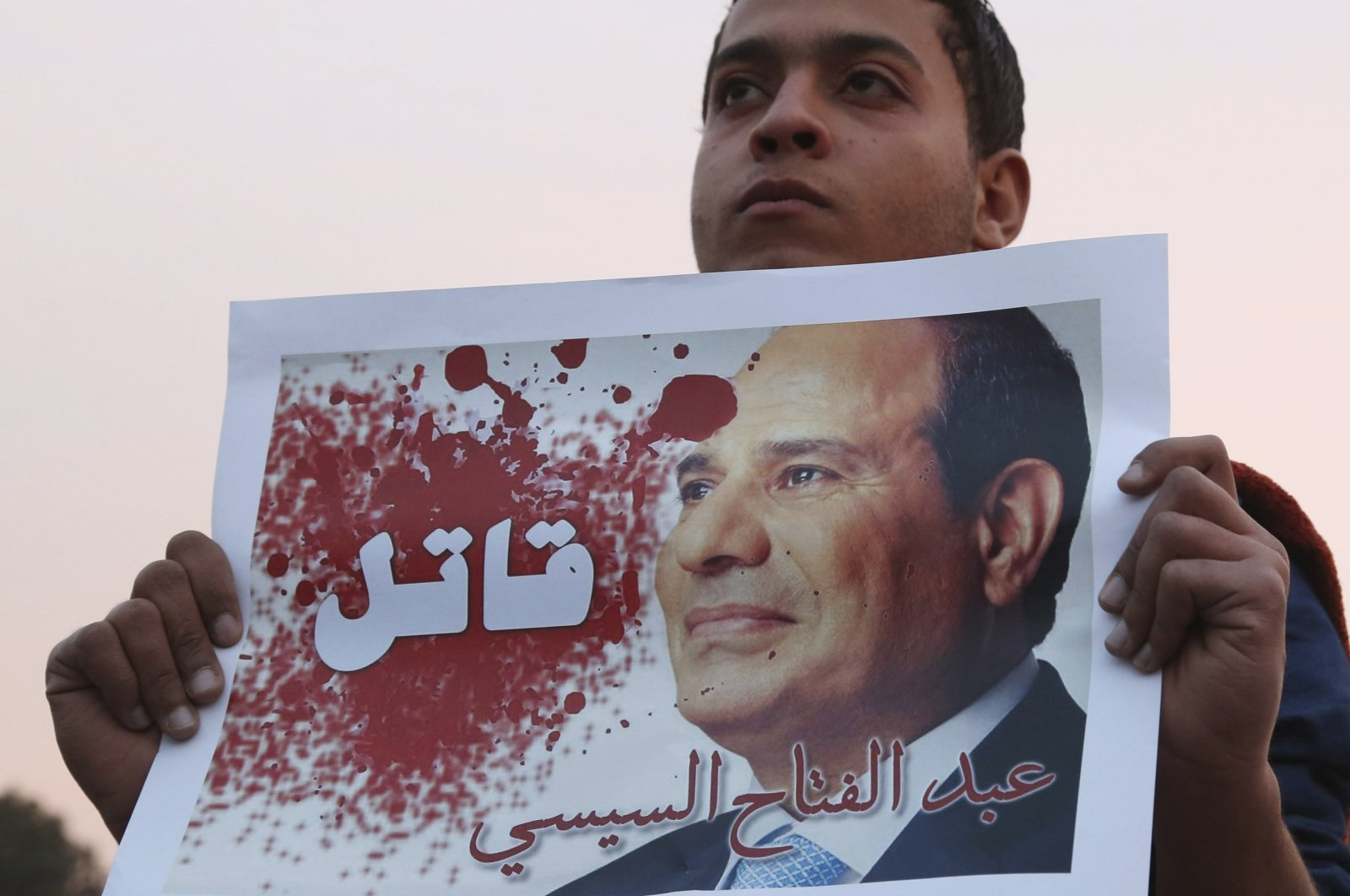 "A man holds a poster of Egyptian President Abdel-Fattah el-Sissi with the word ""Killer"" on it during a silent protest over a bridge, Cairo, Egypt, Feb. 14, 2015. (REUTERS Photo)"