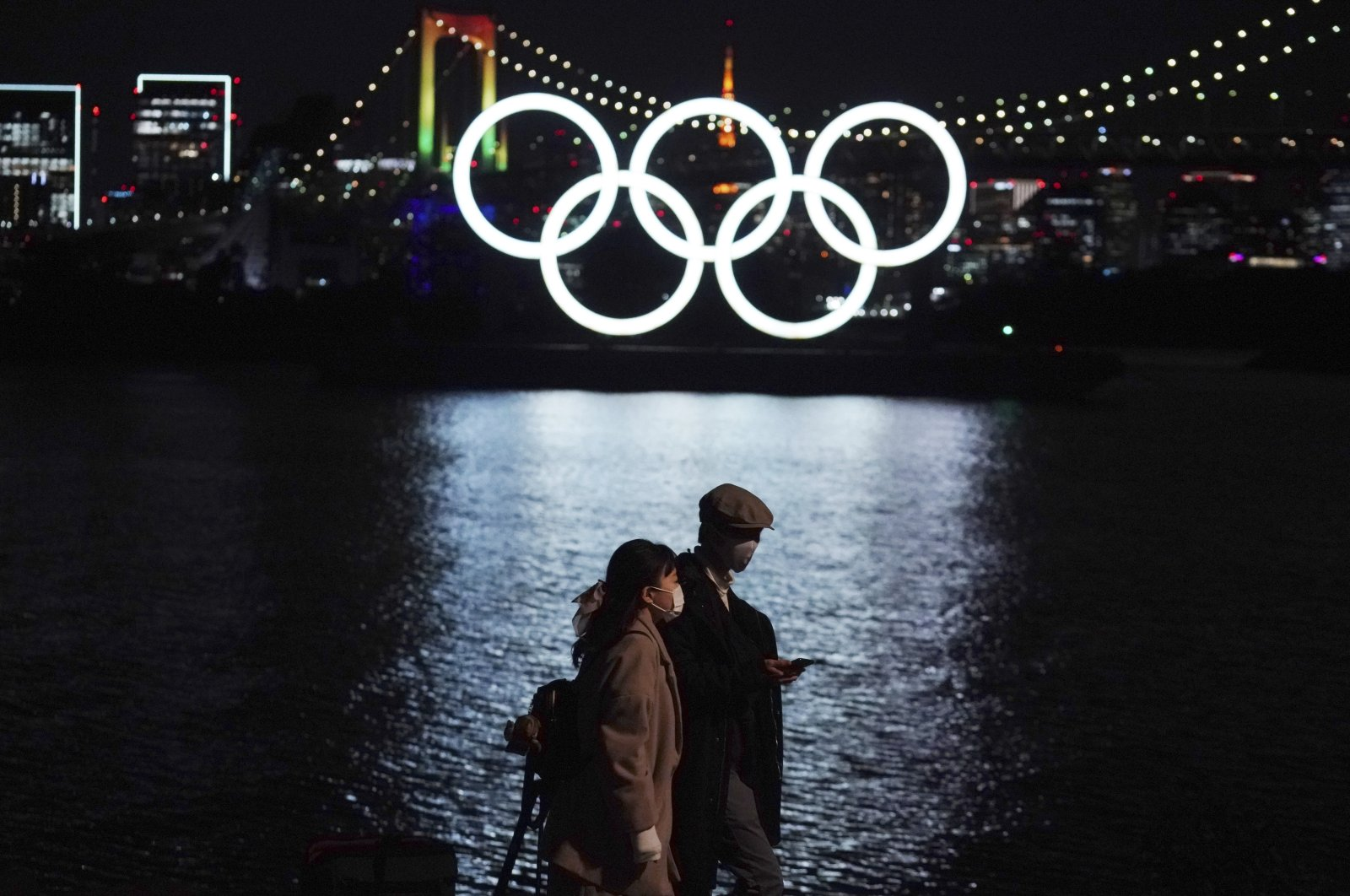 A man and a woman walk past the Olympic rings floating in the water, in Tokyo, Japan, Dec. 1, 2020. (AP PHOTO)