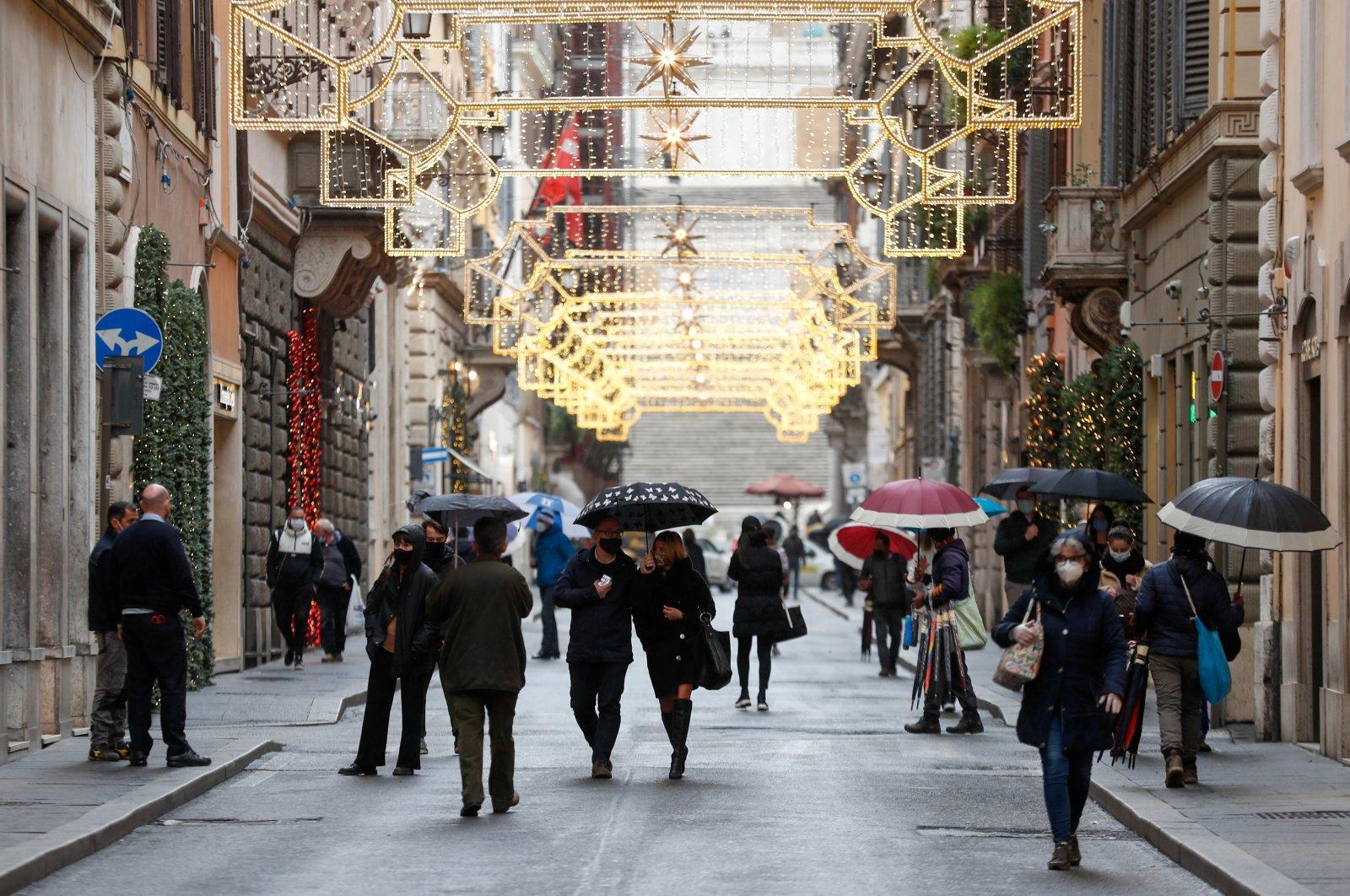 People wearing protective masks walk along Via dei Condotti street, Rome, Italy, Dec. 2, 2020. (Reuters Photo)