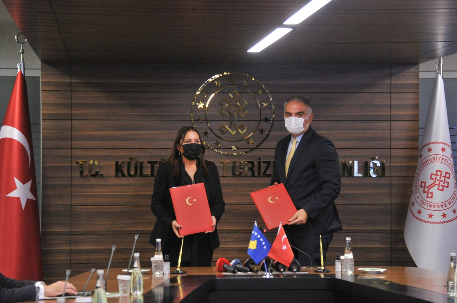 Turkey's Culture and Tourism Minister Mehmet Nuri Ersoy (R) and his Kosovar counterpart Vlora Dumoshi pose with the agreement at the Ministry of Culture and Tourism building in the capital Ankara, Turkey, Dec. 3, 2020. (IHA Photo)